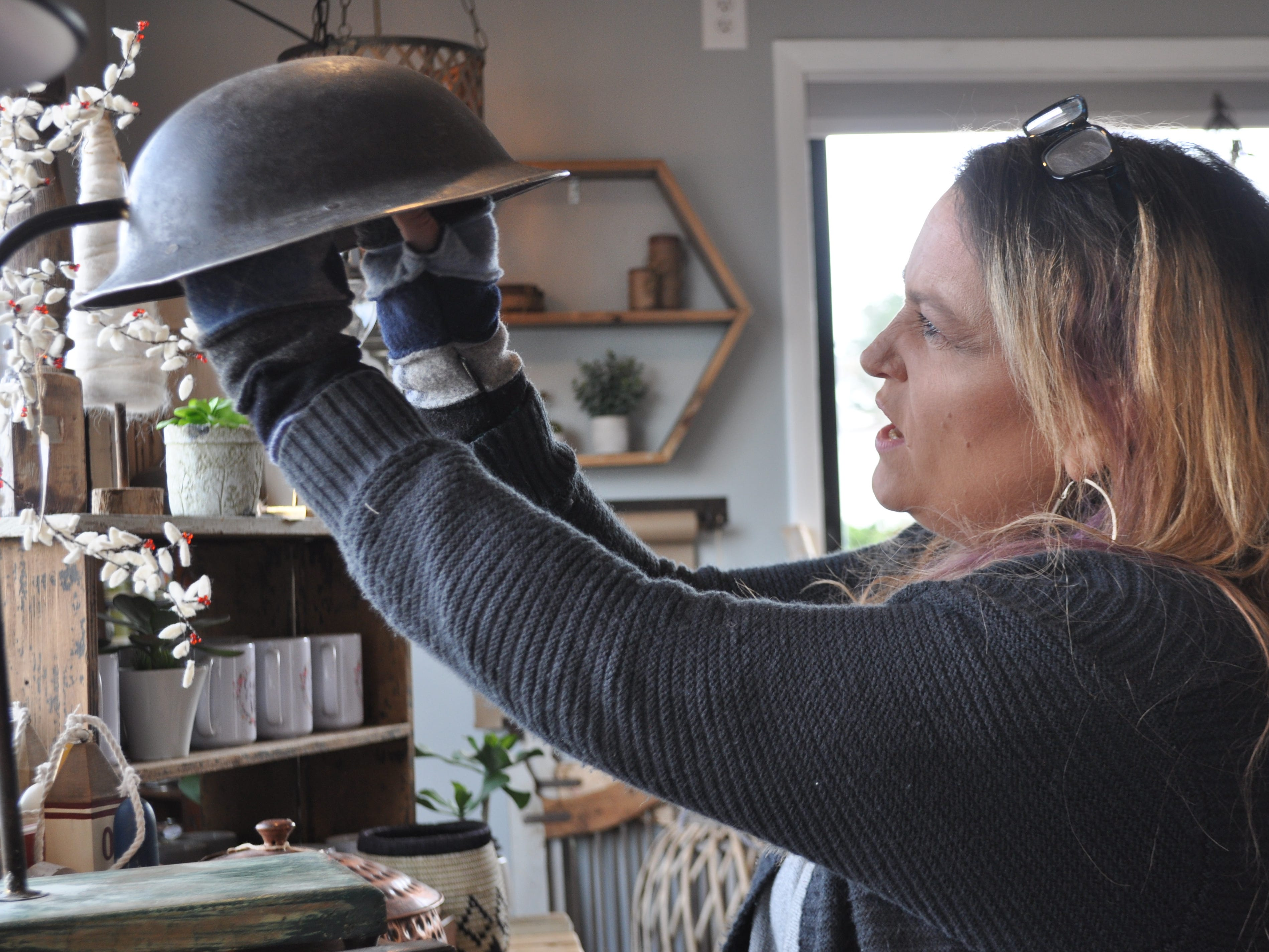 Attics of My Life store owner Ashley Abell tinkers with a handmade lamp made from an army helmet at her Selbyville store on Nov. 14, 2018.
