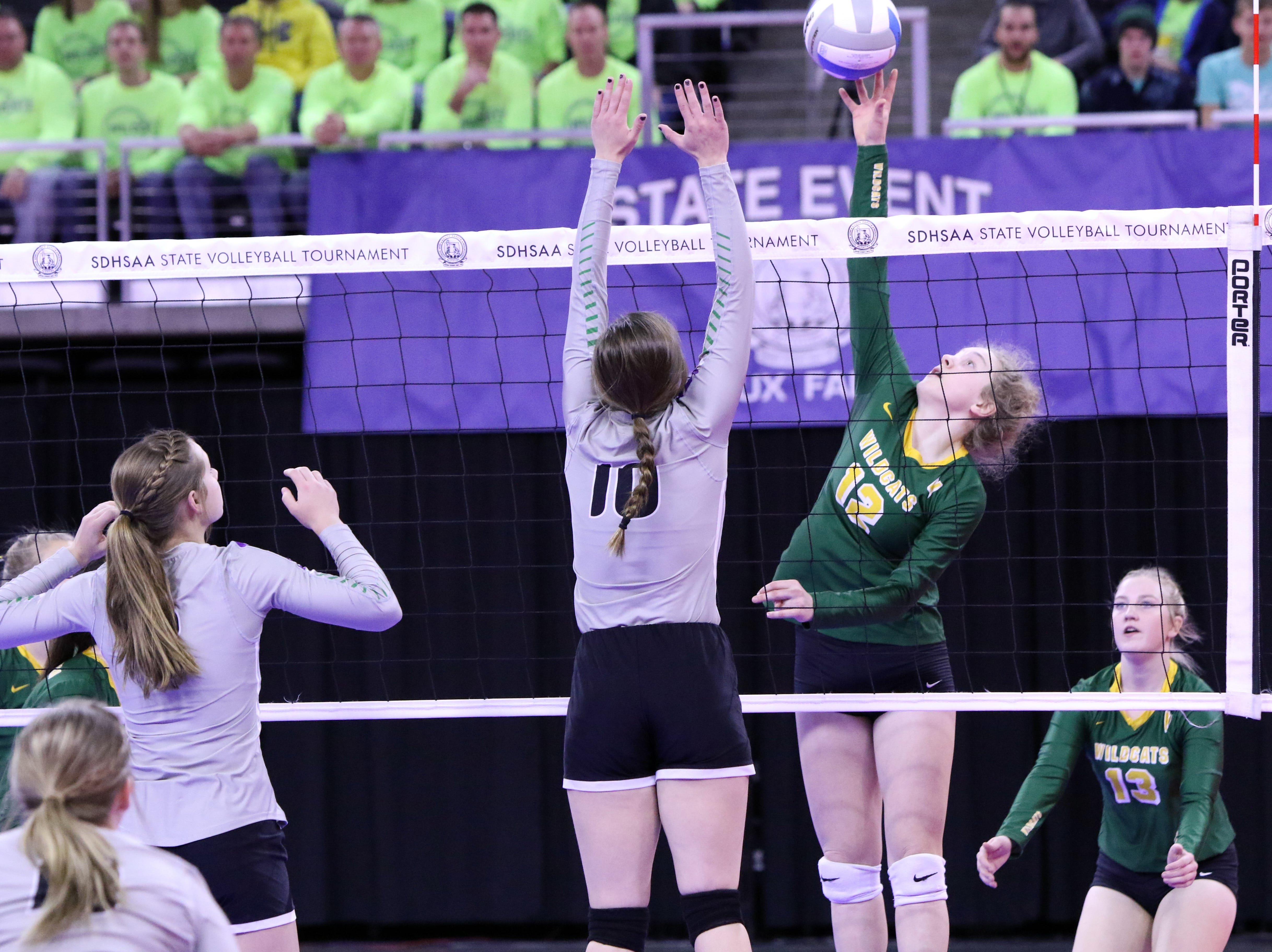 Sydney Schell of Northwestern tips the ball past the defense by Dani Deffenbaugh of Kimball-White Lake during Thursday afternoon's matches in Sioux Falls.