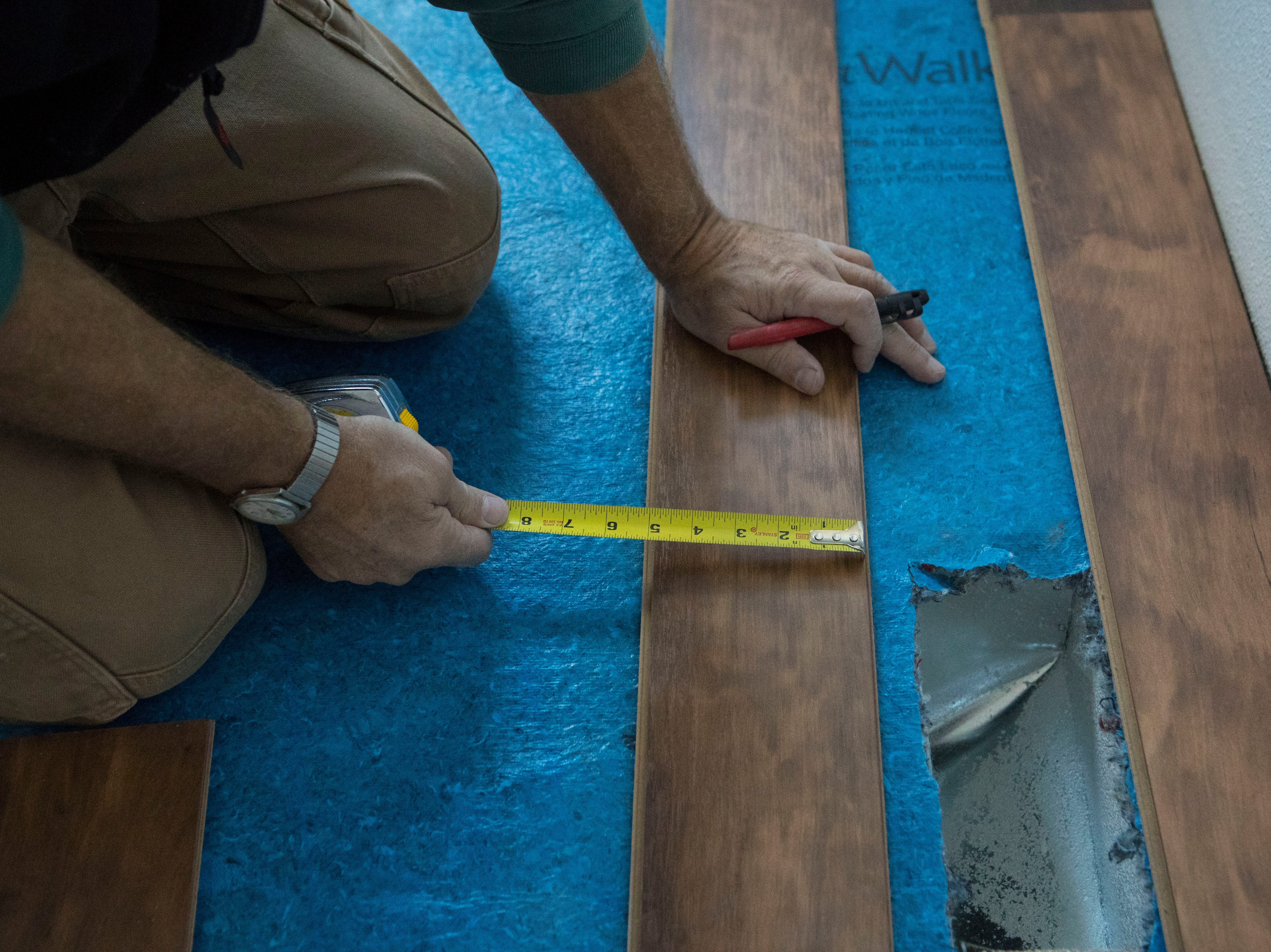 John Homstad, volunteer for Habitat for Humanity, works on the flooring in a house in Sioux Falls, S.D., Thursday, Nov. 15, 2018.