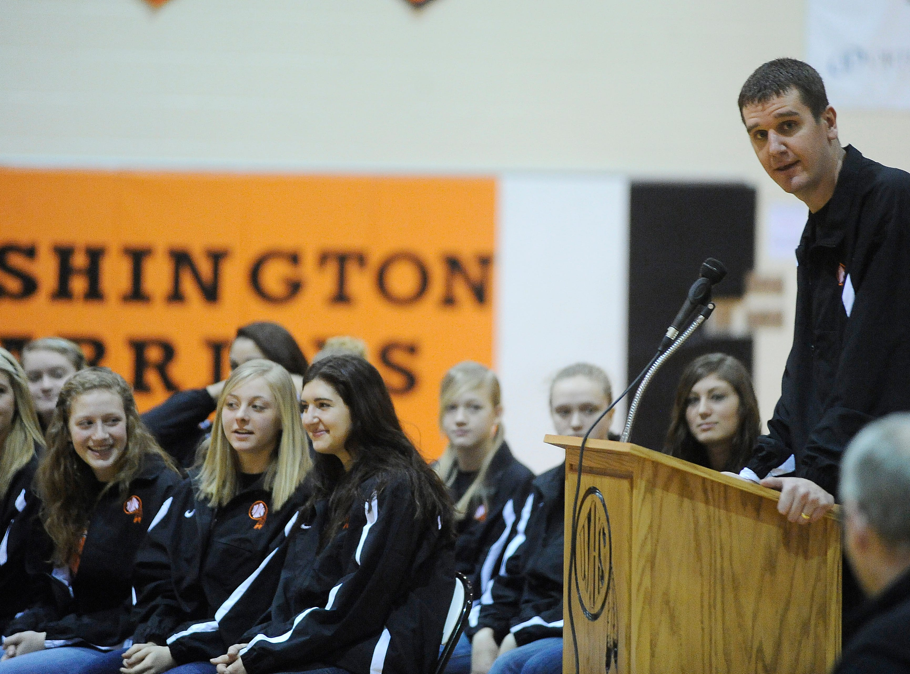 Girls basketball head coach, Nate Malchow says a few words at Sunday's Washington High School celebration after the girls basketball team won the state championship Saturday night.