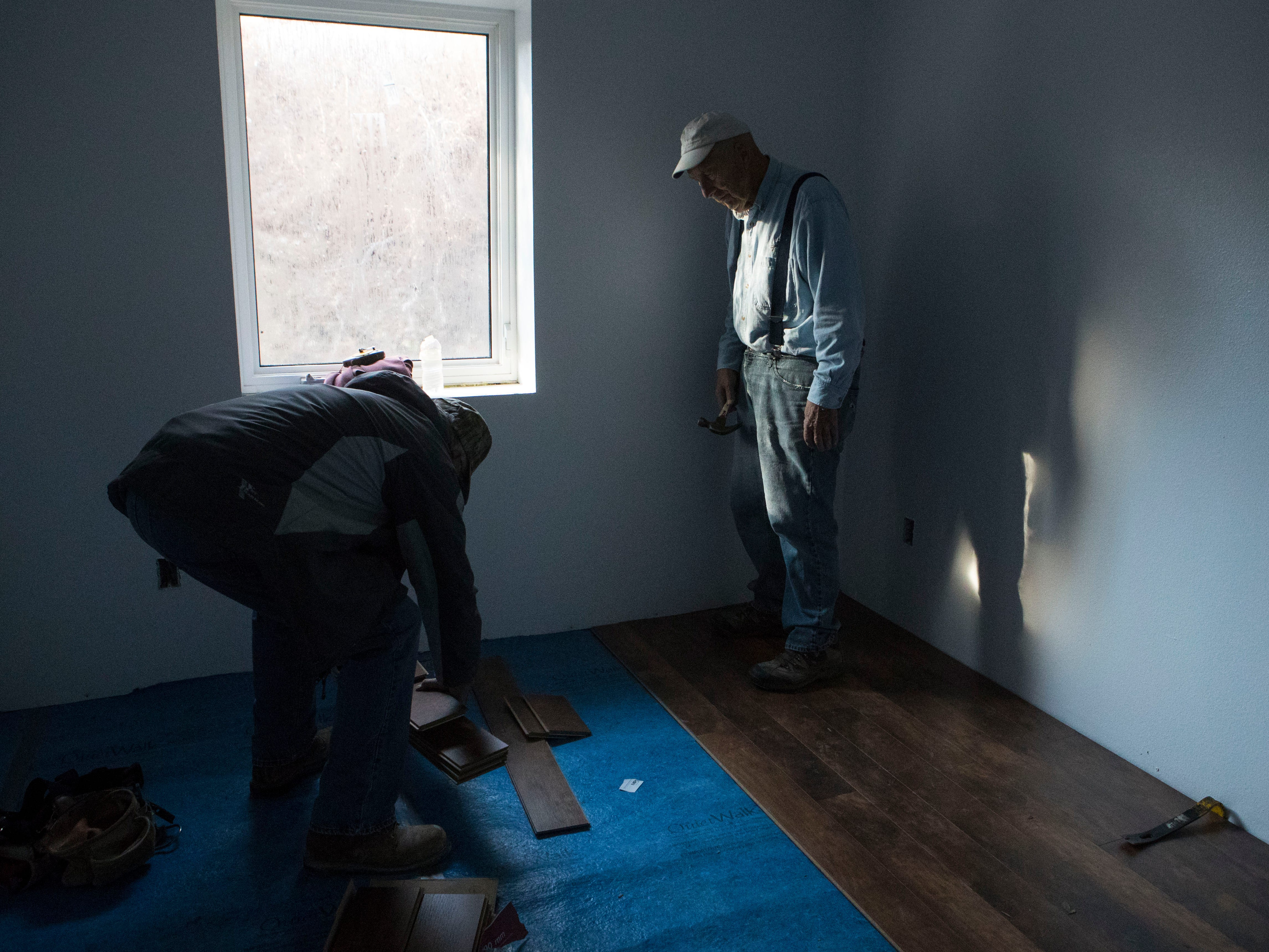Arnie Osmundson (right) and Roger Leistra, volunteers for Habitat for Humanity, work on the flooring in a house in Sioux Falls, S.D., Thursday, Nov. 15, 2018.