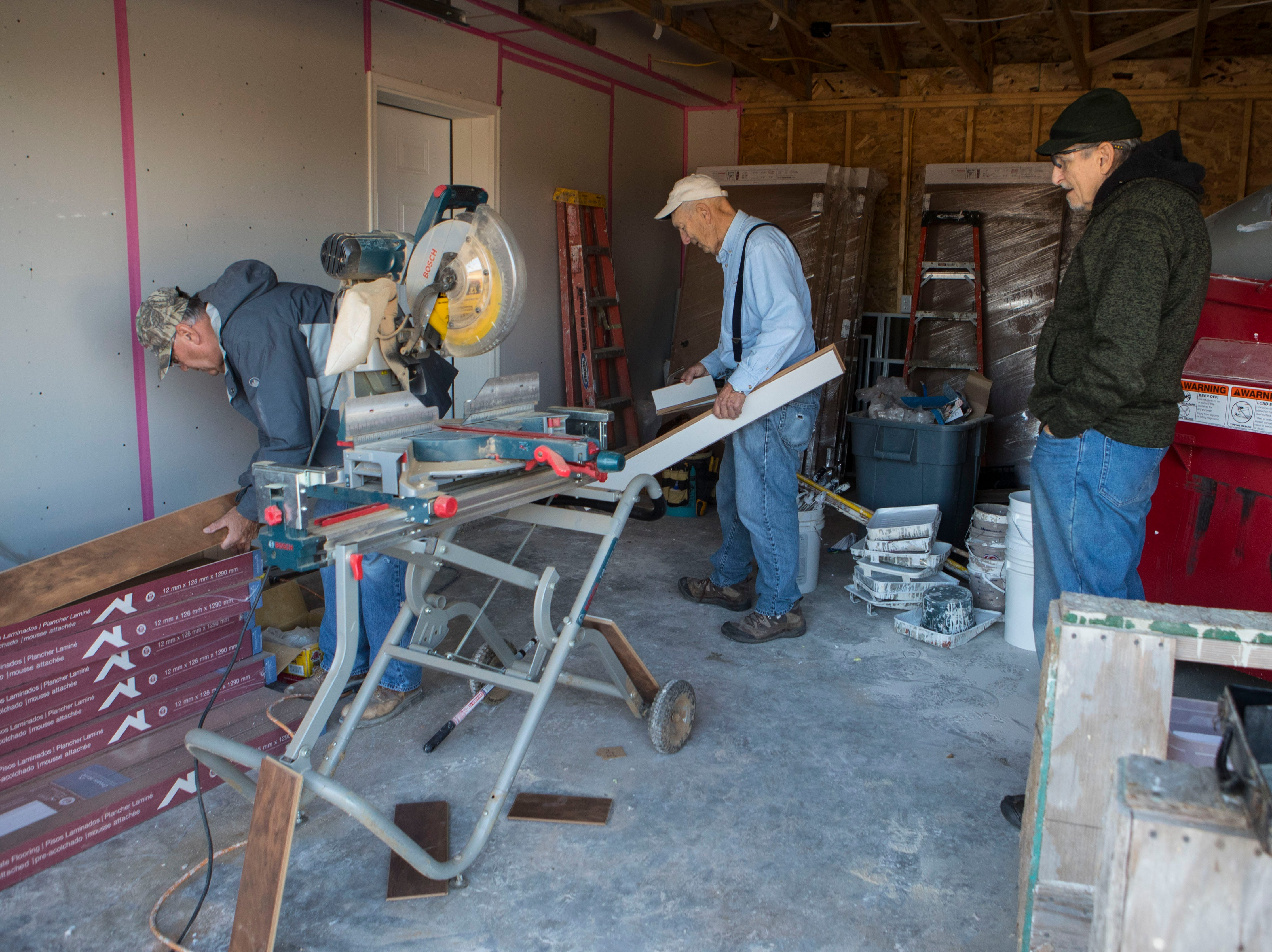 Roger Leistra (left), Arnie Osmundson and Jack Mallek, volunteers for Habitat for Humanity, help build a house in Sioux Falls, S.D., Thursday, Nov. 15, 2018.