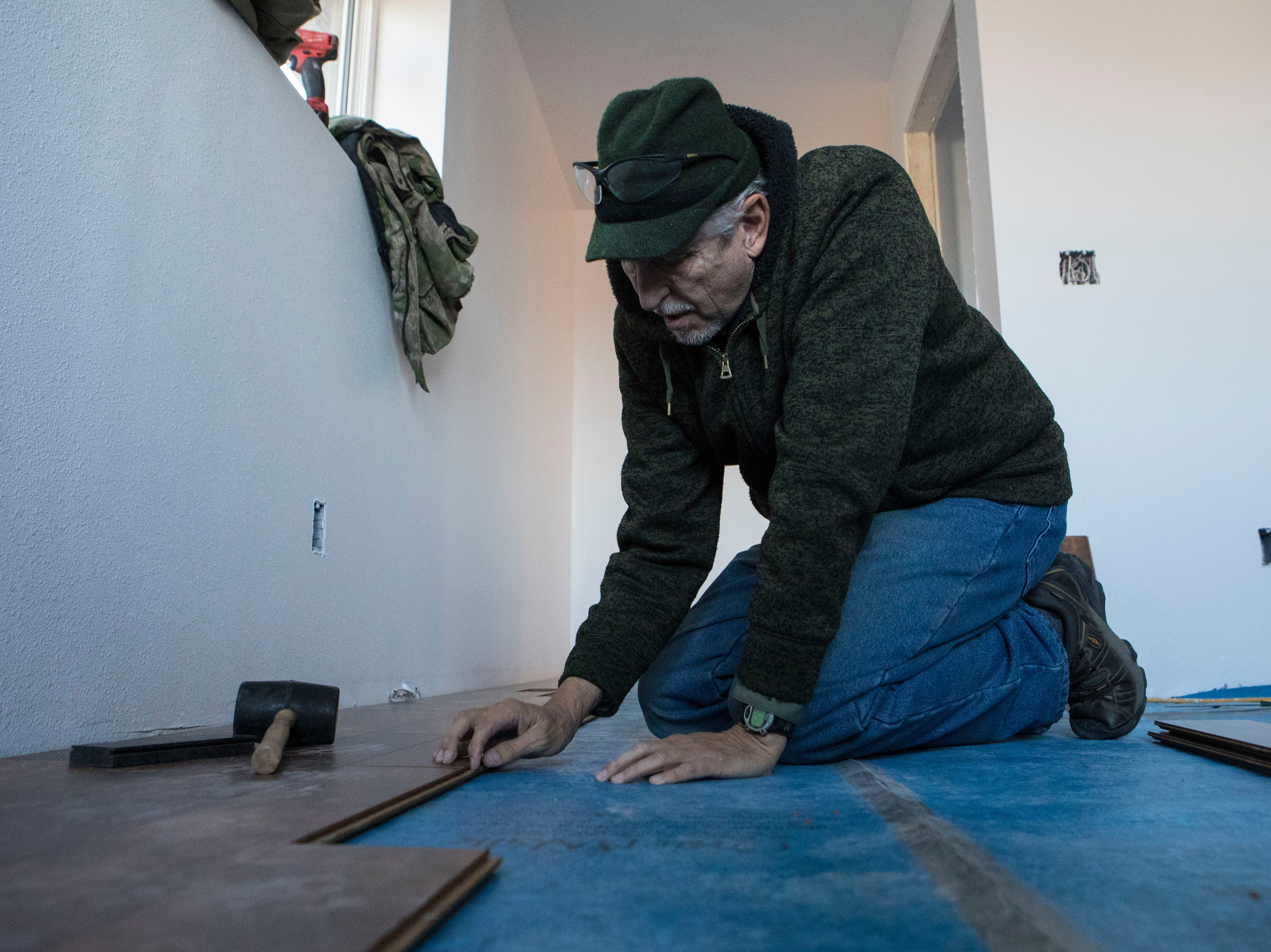 Jack Mallek, volunteer for Habitat for Humanity, works on the flooring in a house in Sioux Falls, S.D., Thursday, Nov. 15, 2018.