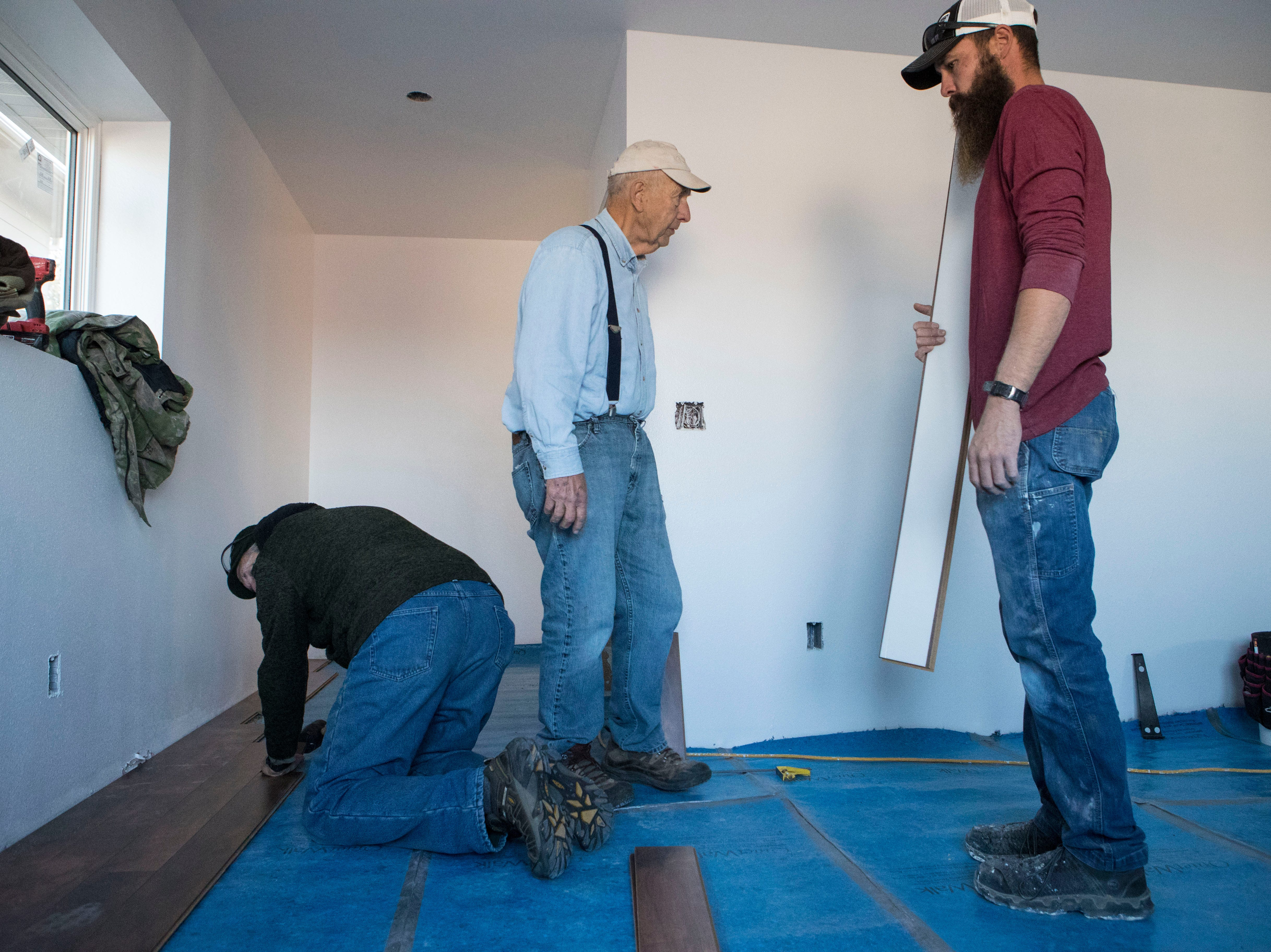Jack Mallek (left), Arnie Osmundson and Construction Foreman Dustin Kuhl work on the flooring in a house in Sioux Falls, S.D., Thursday, Nov. 15, 2018.
