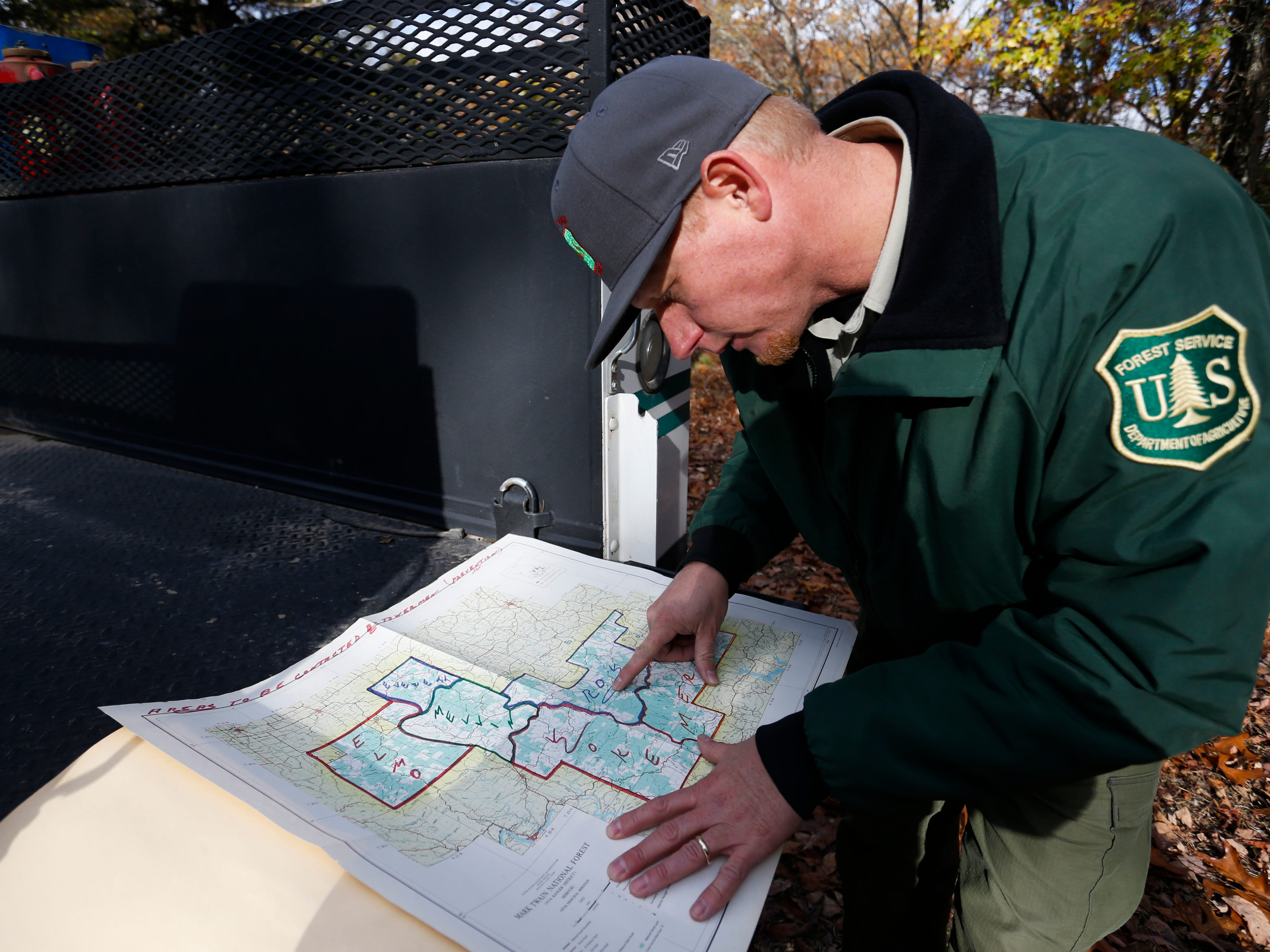 Reggie Bray, a Forest Service fire management officer, shows the locations of fire towers on old Forest Service maps.