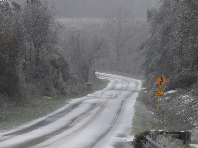 View of an icy Barterbrook Road as sleet continues to fall Sleet mixed with rain falls as a snowplow with the Virginia Department of Transportation travels with plow raised on U.S. 250 on Thursday, Nov. 15, 2018.