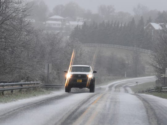 A driver travels slowly along an ice covered Barterbrook Road as sleet continues to fall on Thursday, Nov. 15, 2018.