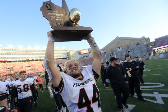 Iola-Scandinavia's Bryce Huettner (44) holds up the championship trophy after the Thunderbirds defeated Racine Lutheran in the WIAA Division 6 championship game at Camp Randall Stadium on Thursday, November 15, 2018 in Madison, Wis.