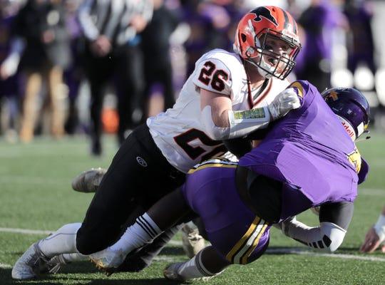 Iola-Scandinavia's Carter Kurki (26) tackles Racine Lutheran's Jeylen Houston (8) during the WIAA Division 6 state championship game.