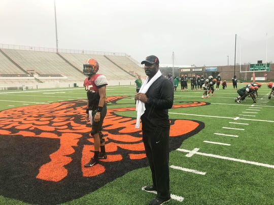 FAMU head coach Willie Simmons watches his team prep for the Florida Classic with backup quarterback D.J. Phillips. The Rattlers worked out in the rain this week for the game.