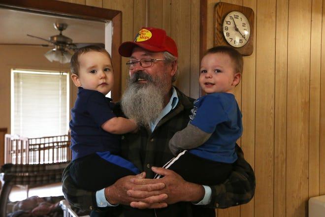 Kenneth Williams holds two of his grandsons, Lucas Prescott, 1, left, and Axel Frascona, 1, in his home in Grand Ridge, Fla., Thursday, Nov. 15, 2018.