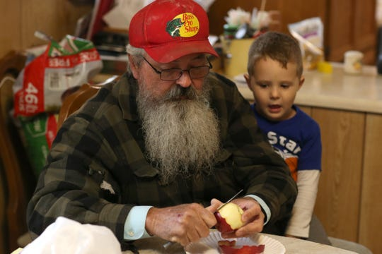 Kenneth Williams, a U.S. postal worker of 32 years, cuts an apple for his grandson Braxton Prescott, 3, in their home in Grand Ridge, Fla. Thursday, Nov. 15, 2018.