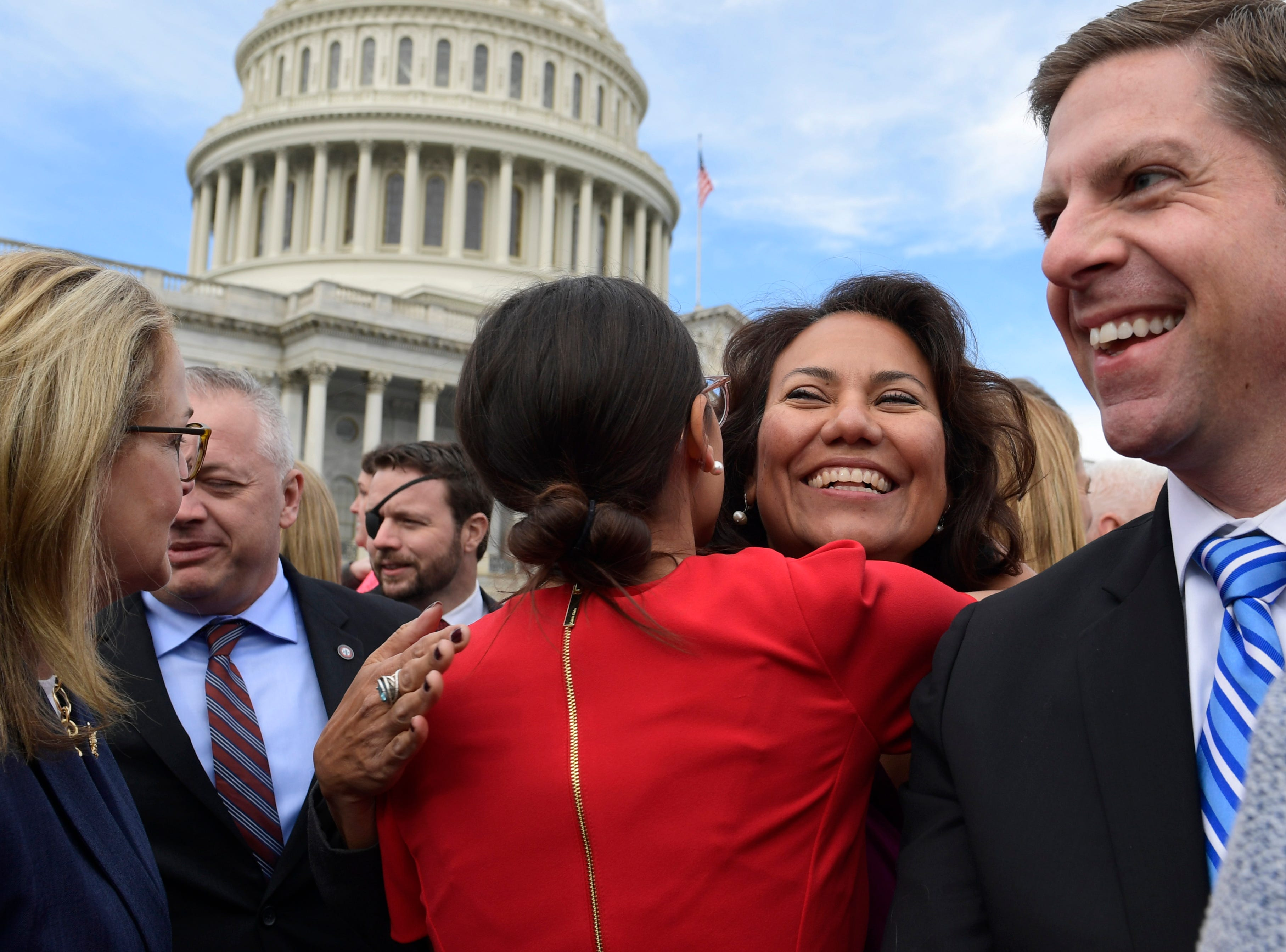 U.S. Rep.-elect Alexandria Ocasio-Cortez, D-N.Y., center in red, gets a hug from U.S. Rep.-elect Veronica Escobar, D-El Paso, on Wednesday, Nov. 14, 2018, after a photo opportunity with the freshman class on Capitol Hill in Washington, D.C.