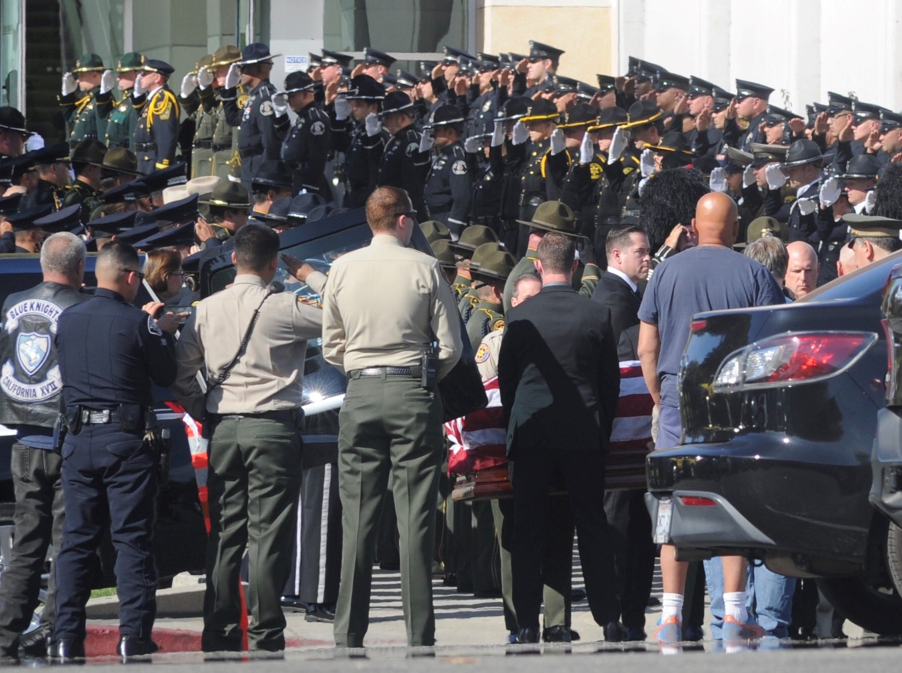 Officers stand at attention and salute as the casket carrying Ventura County Sheriff's Office Sgt. Ron Helus arrives for his memorial service at Calvary Community Church in Westlake Village on Thursday.