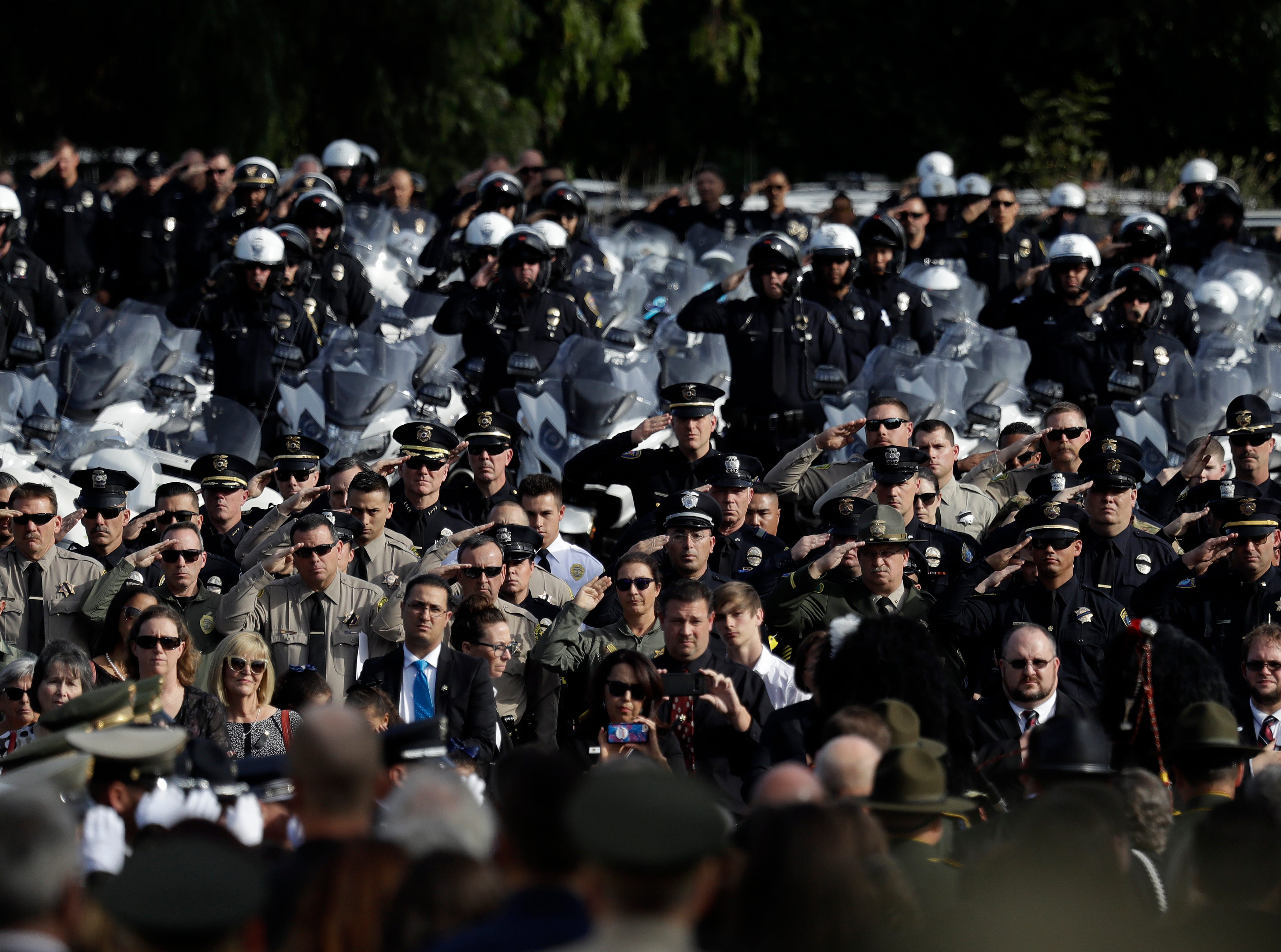 Law enforcement personnel salute as the casket of Ventura County Sheriff's Office Sgt. Ron Helus is carried out after his memorial service at Calvary Community Church in Westlake Village on Thursday.