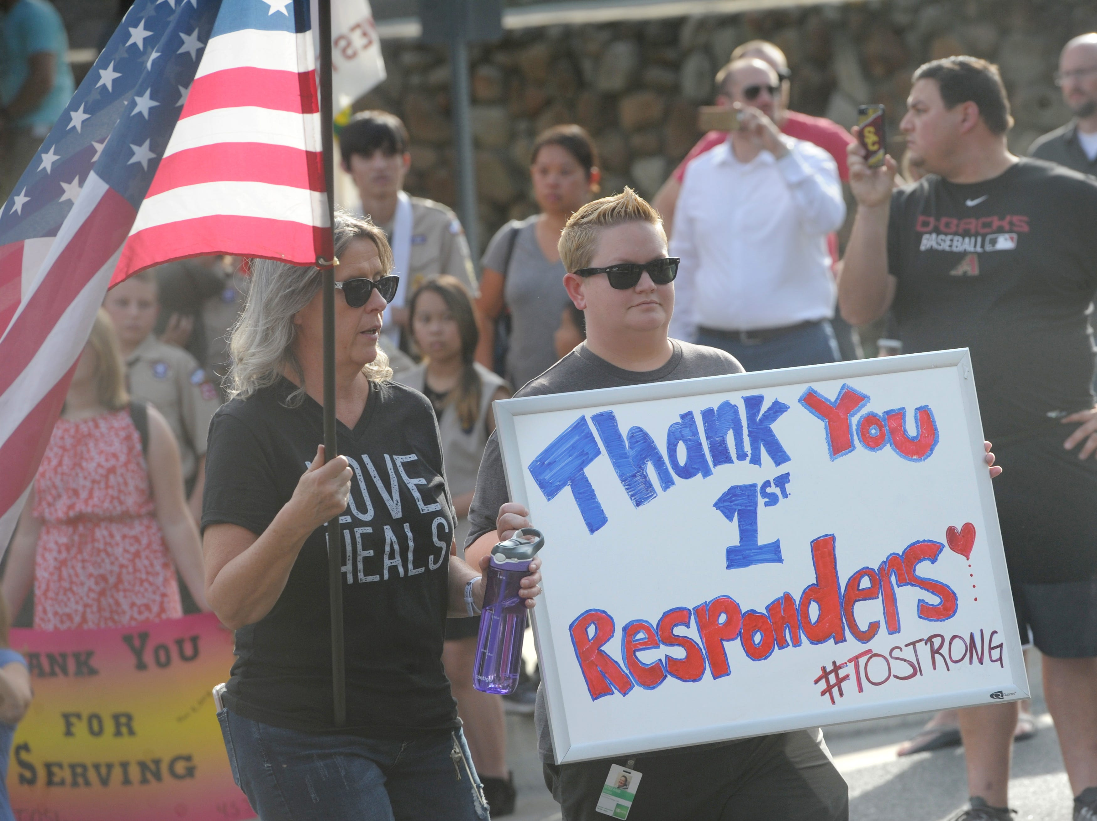 Eileen Mayfield, left, and Stefanie Moses hold a sign and an American flag at the funeral procession for Ventura County Sheriff's Office Sgt. Ron Helus at Pierce Brothers Valley Oaks Memorial Park in Westlake Village on Thursday.