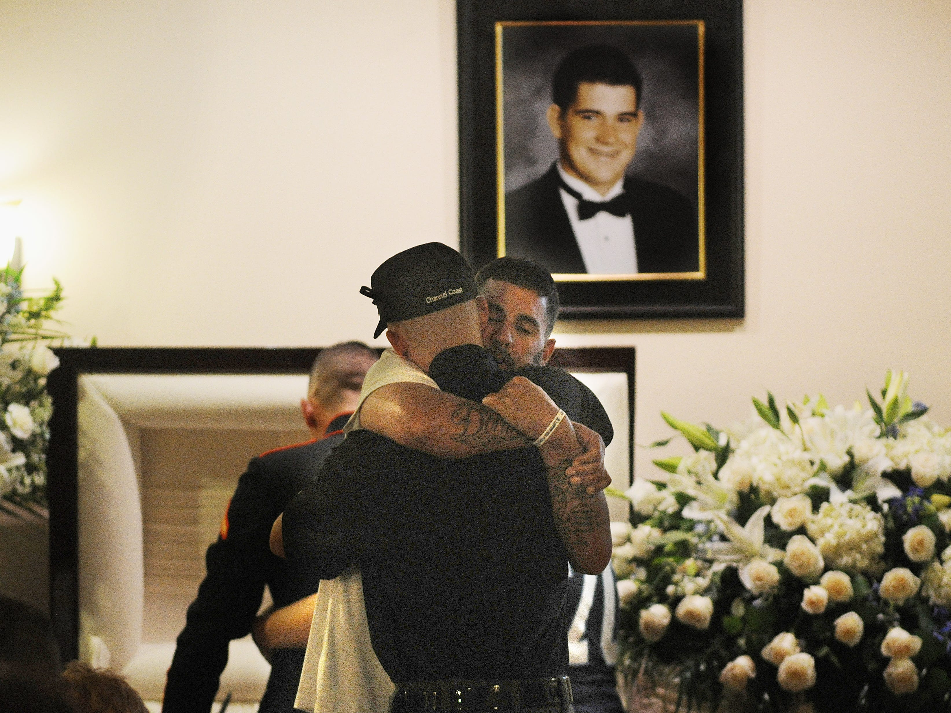 Jason Coffman, facing camera, father of Cody Coffman, gets a hug from a friend in front of the casket at a memorial service in honor of Cody, who was killed in the Borderline shooting in Thousand Oaks. About 1,000 people attended the service at the Perez Family Chapel.