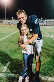Central Valley Christian's Grant Highstreet poses with his sister, Lizzy, during a Cavaliers' football game.