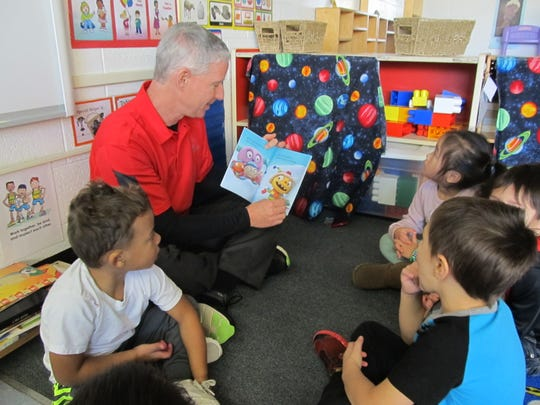 Children listen as a volunteer from Domtar in Rothschild reads a book at Head Start in Wausau.