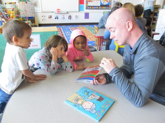 Preschool students at Head Start in Wausau look at a book with a volunteer from Domtar in Rothschild.