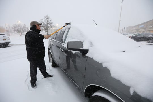 Ed Ferrara of New Jersey cleans the snow from his car at the Rockland Plaza in Nanuet.