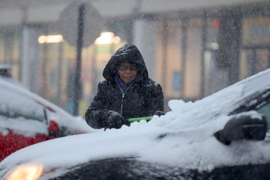 Antoinette Jean-Joseph of Pomona clears the snow from her car at the Rockland Plaza in Nanuet.