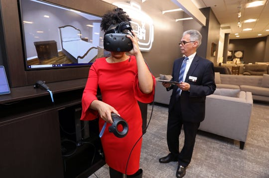 Media relations director Emily Hawkins tries the new virtual reality technology with help from sales associate Enrique Velilla which allows clients to envision the furniture within their home at Macy's in Yonkers Nov. 15, 2018.
