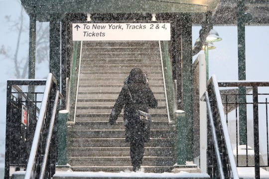 A Metro-North commuter takes the stairs to the New York City-bound platform at the Tarrytown Metro-North station during a steady snowfall Nov. 15, 2108.