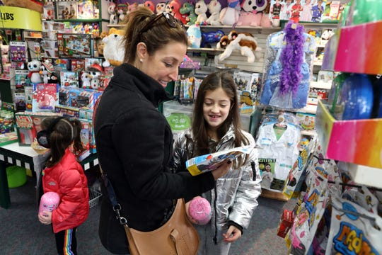 Allie Rosenberg, 8, of Scarsdale shows her mother, Jessica Rosenberg, a building dough she likes while shopping at the Learning Express toy store in Scarsdale Nov. 12, 2018.