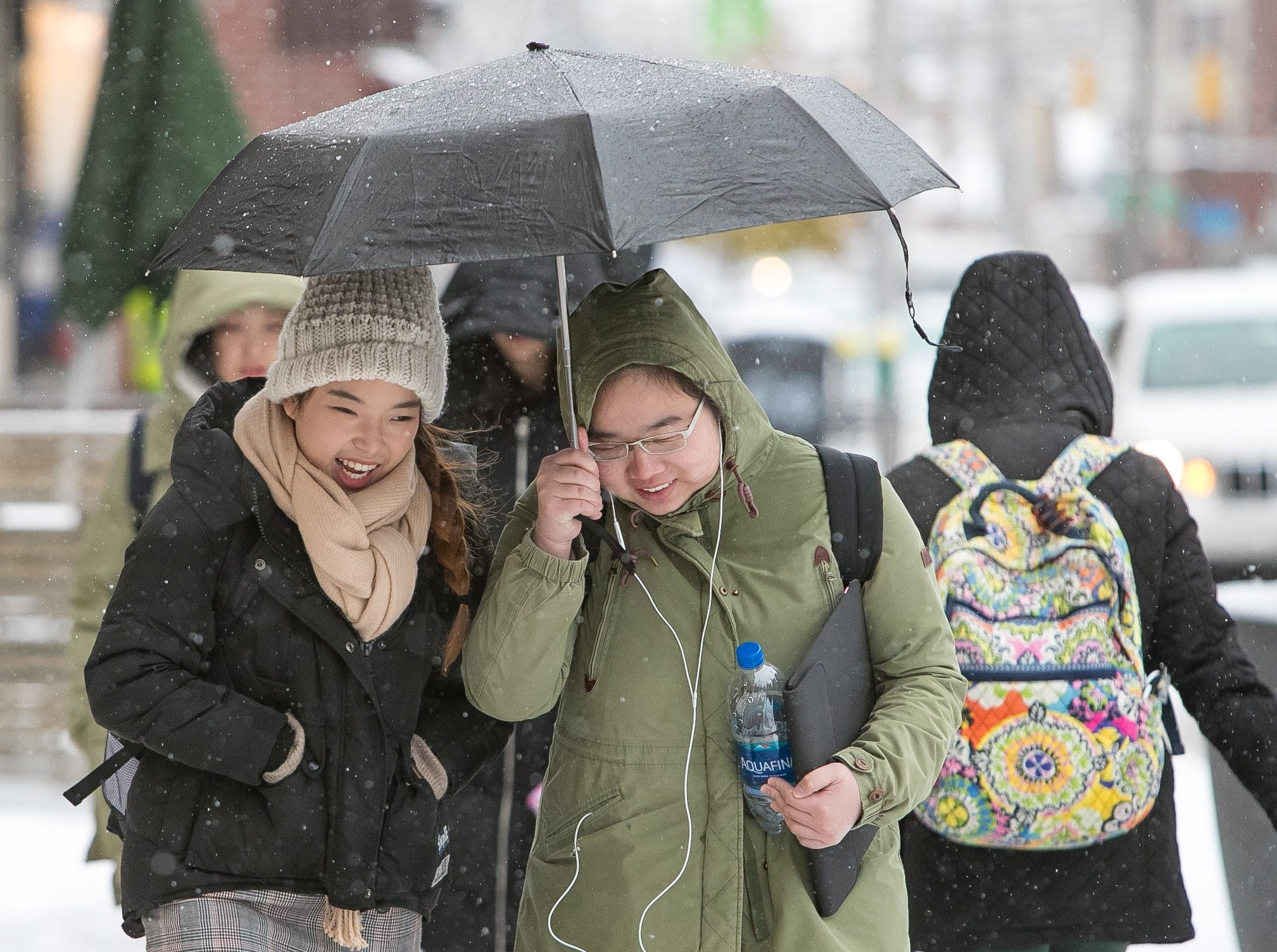 University of Delaware students walk through the snow along Main Street as classes close at 2:30pm due to the weather.