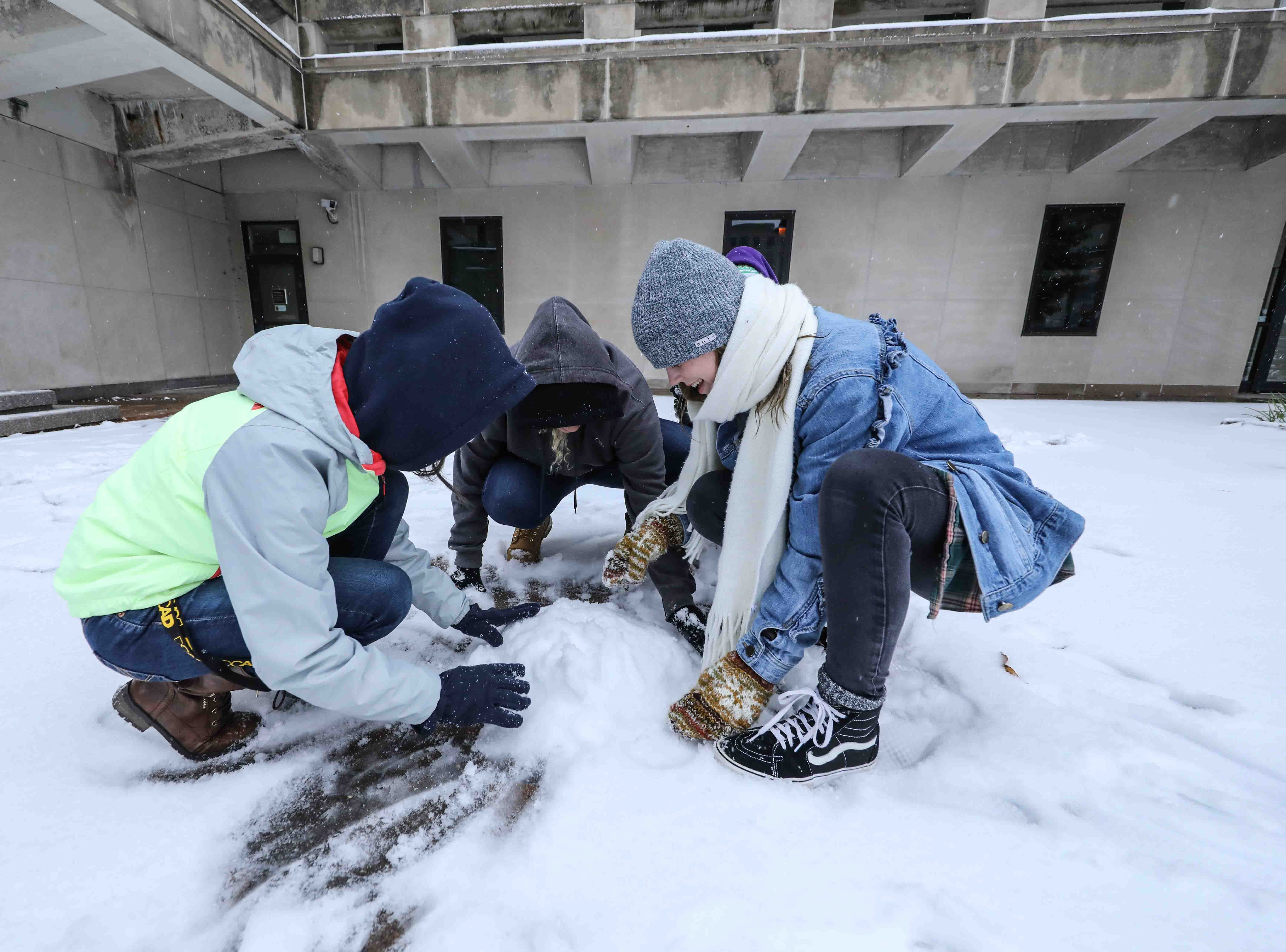 A group of teenagers attempt to build a snowman during a November snowfall on Thursday, Nov. 15, 2018, in Wilmington.