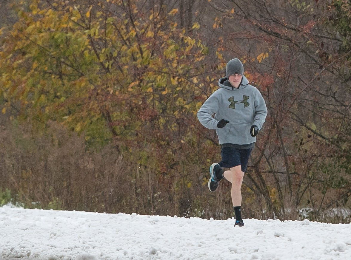 A runner jogs in shorts along Valley Road in Hockessin as snow rolls into Delaware and the surrounding area.