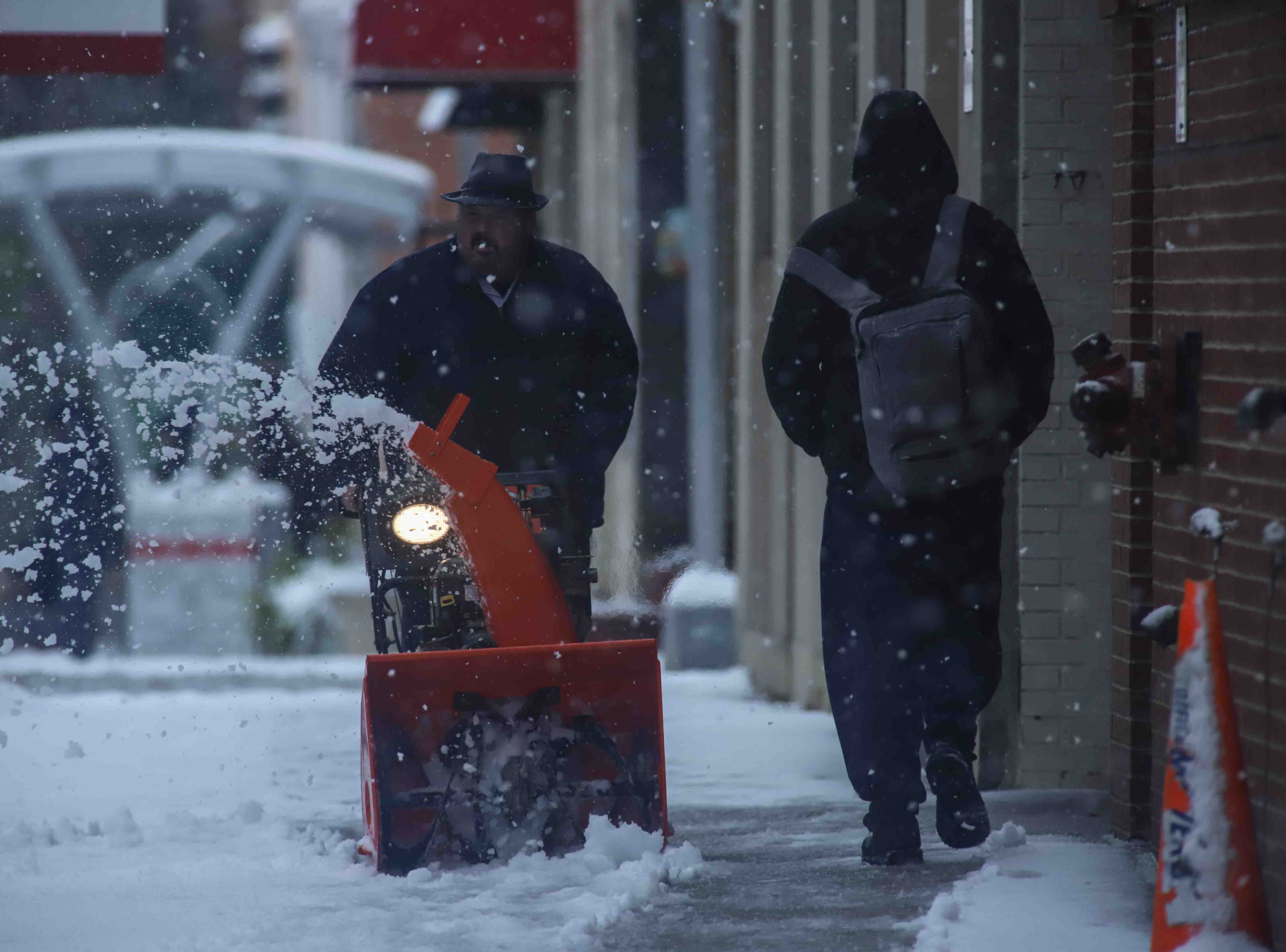 Maintenance crews begin to remove snow from the sidewalks of North King Street during heavy snowfall on Thursday, Nov. 15, 2018, in Wilmington.