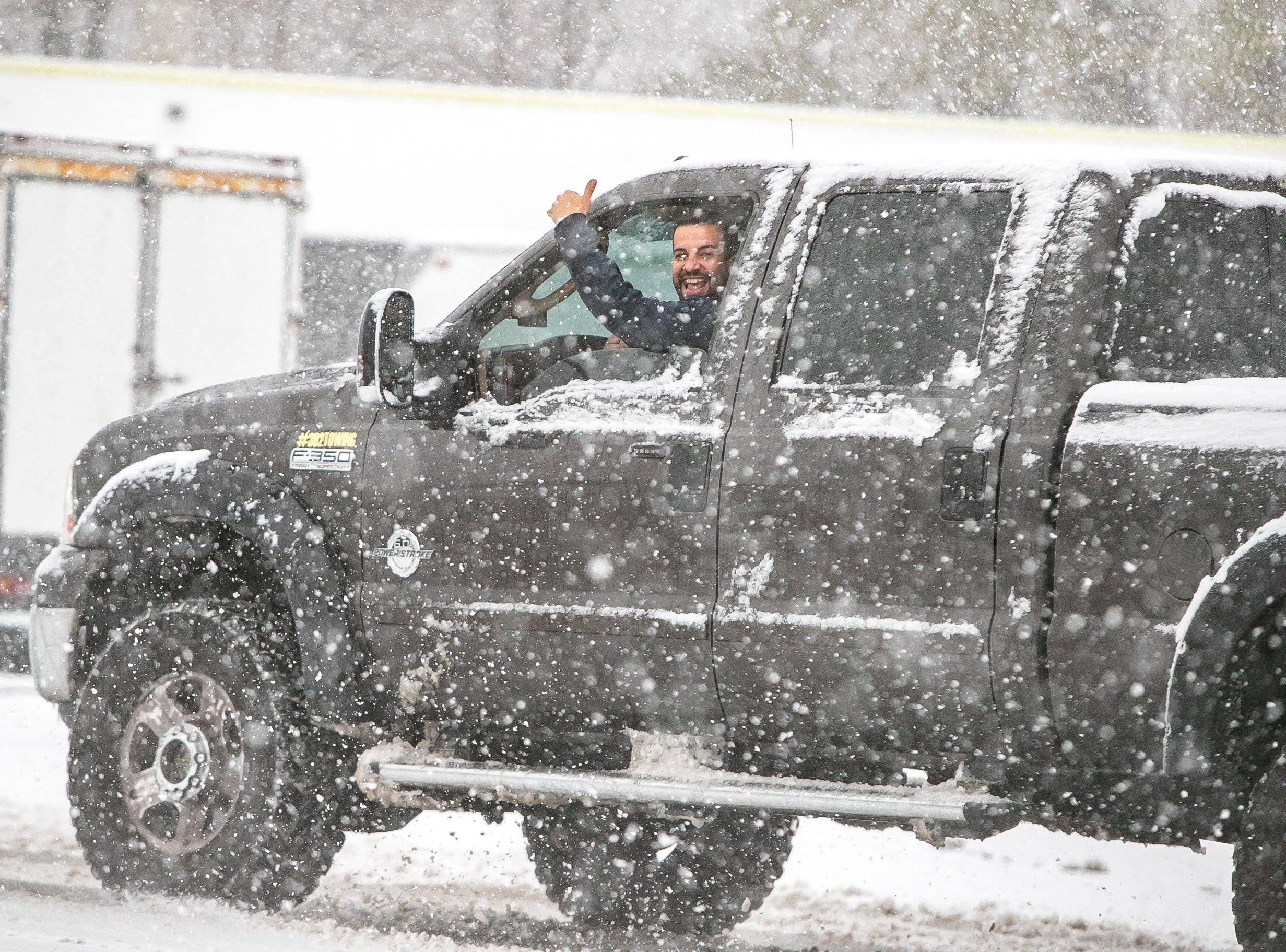A driver gives a thumbs up in the snow as he drives along Lancaster Pike in Hockessin.