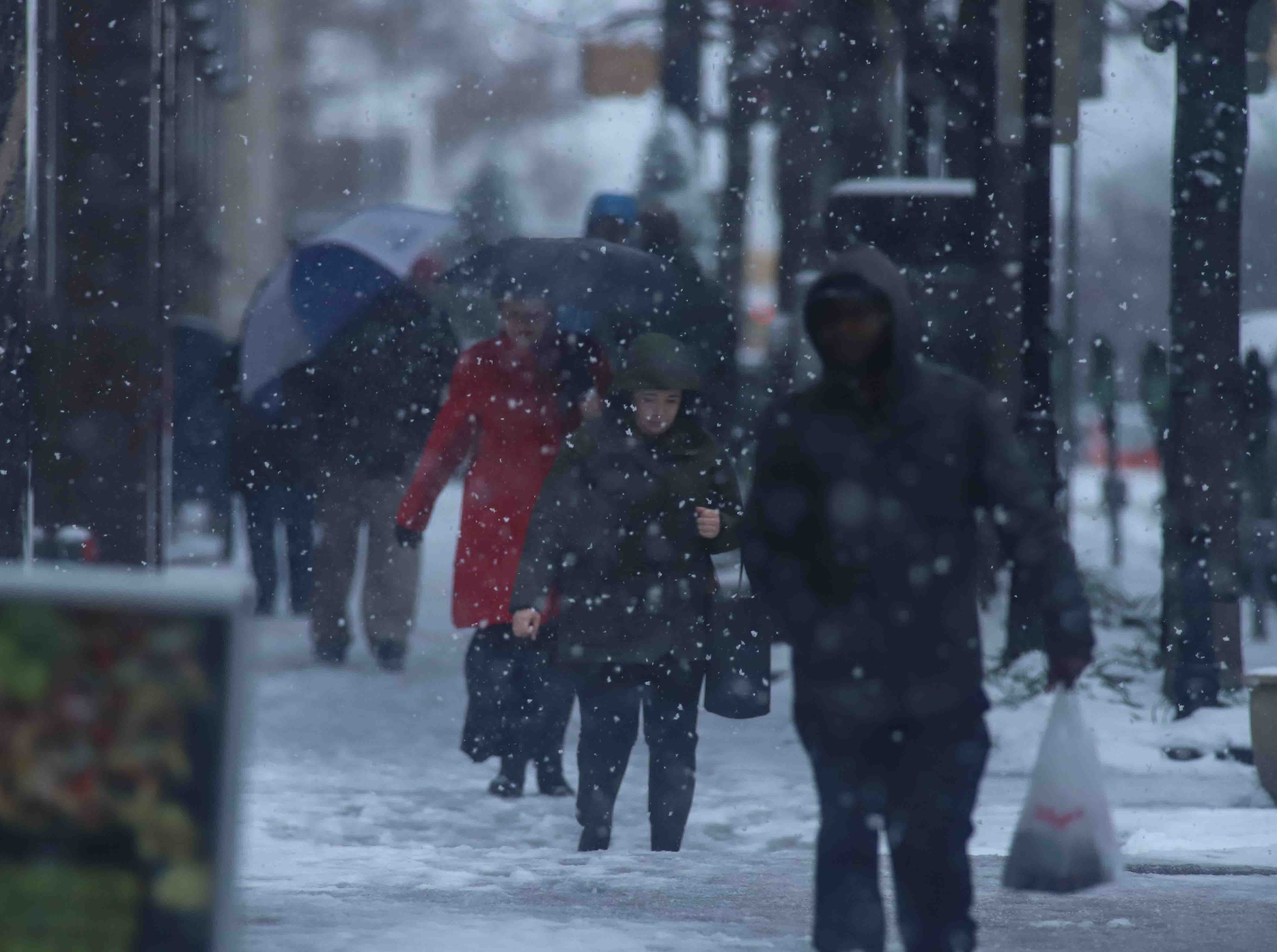 Pedestrians walking down Market Street during heavy snowfall on Thursday, Nov. 15, 2018, in Wilmington.