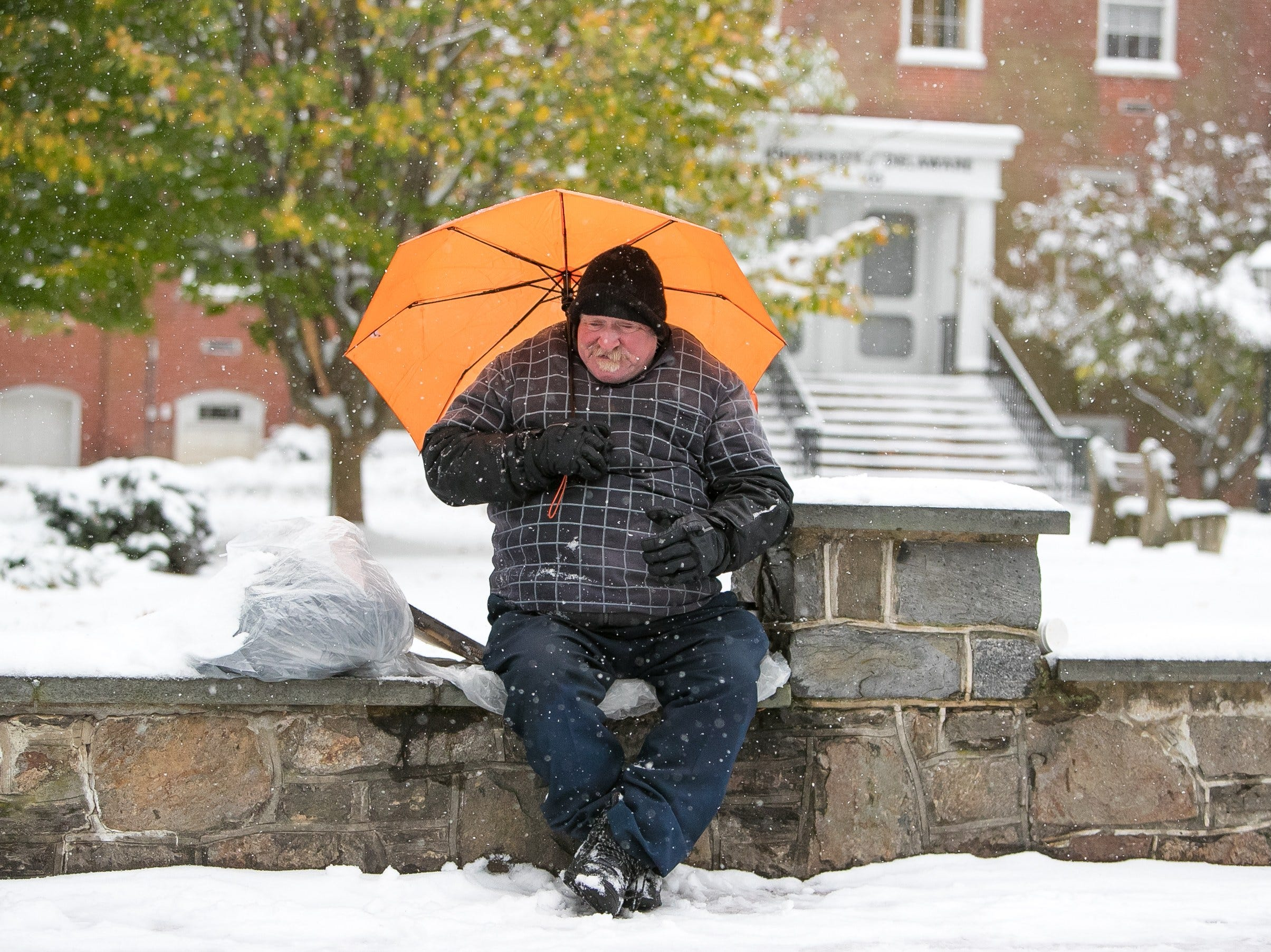A man sits in the falling snow on Main Street in Newark as snow rolls into Delaware and the surrounding area.