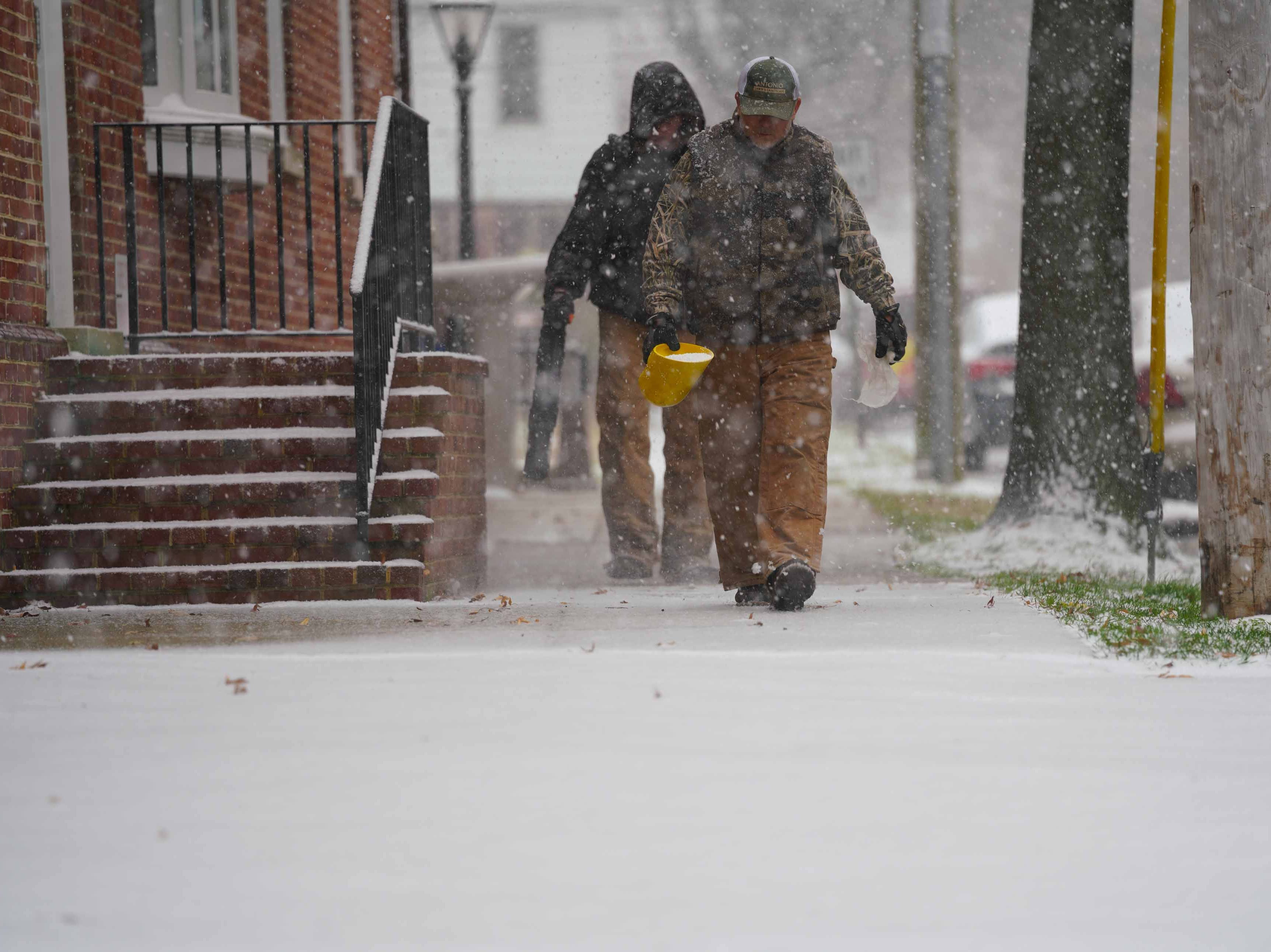 Workers help clear snow from side walks on E. 5th St. in Old New Castle on Thursday morning.