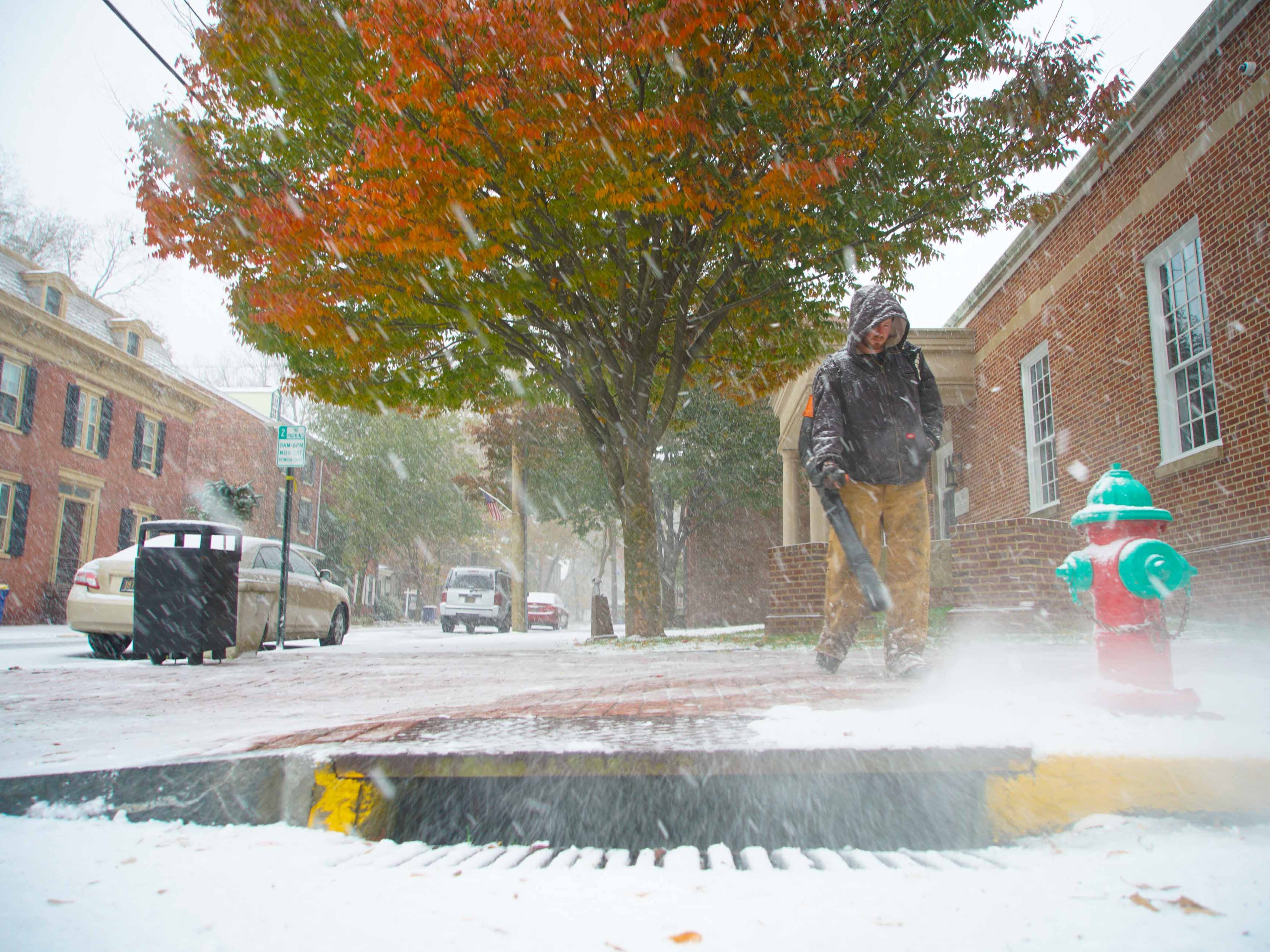 Curtis Penland blows falling snow from sidewalks in front of the New Castle Public Library in Old New Castle on Thursday morning.