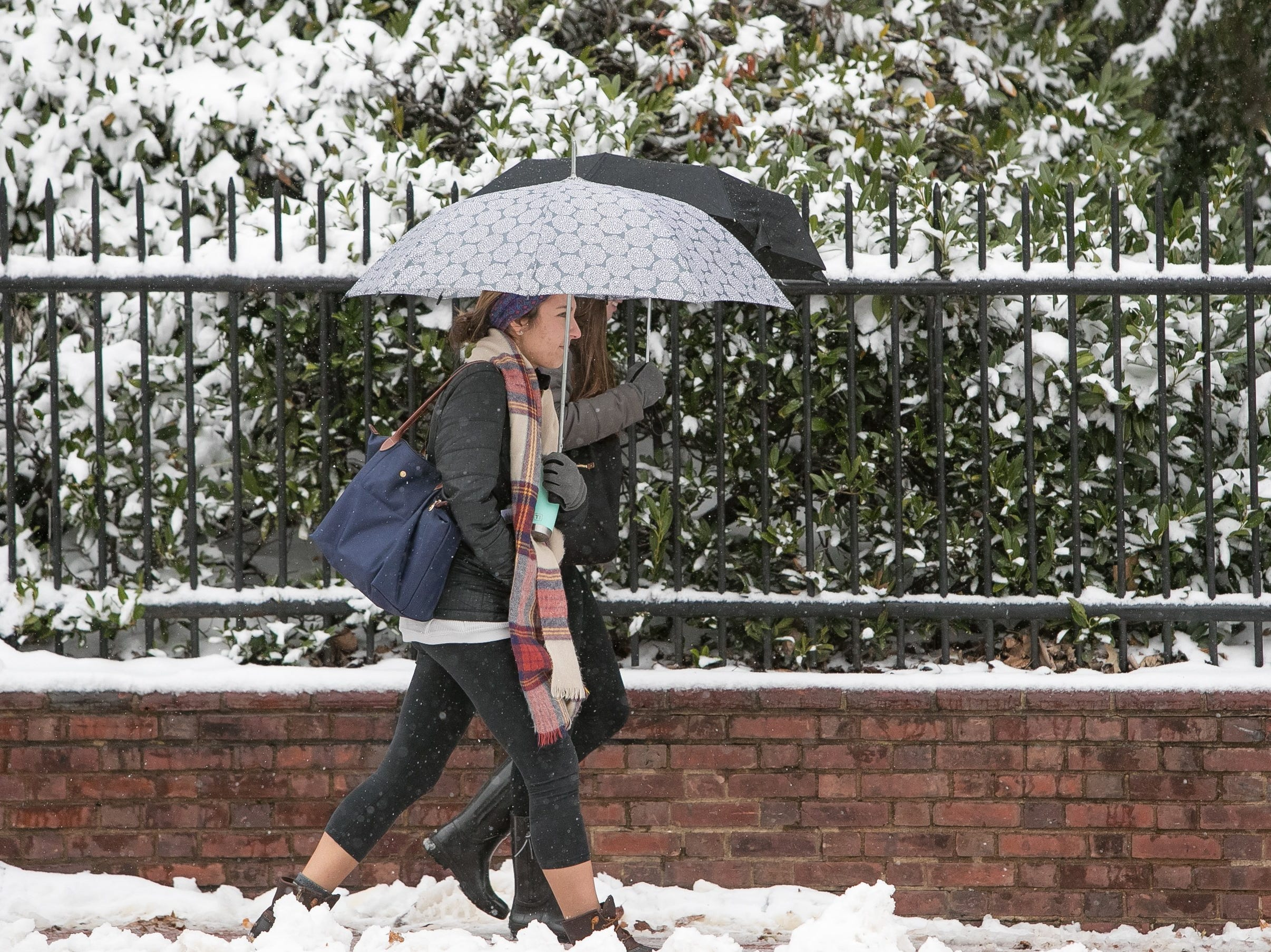 University of Delaware students walk through the snow as classes close at 2:30pm due to the weather.