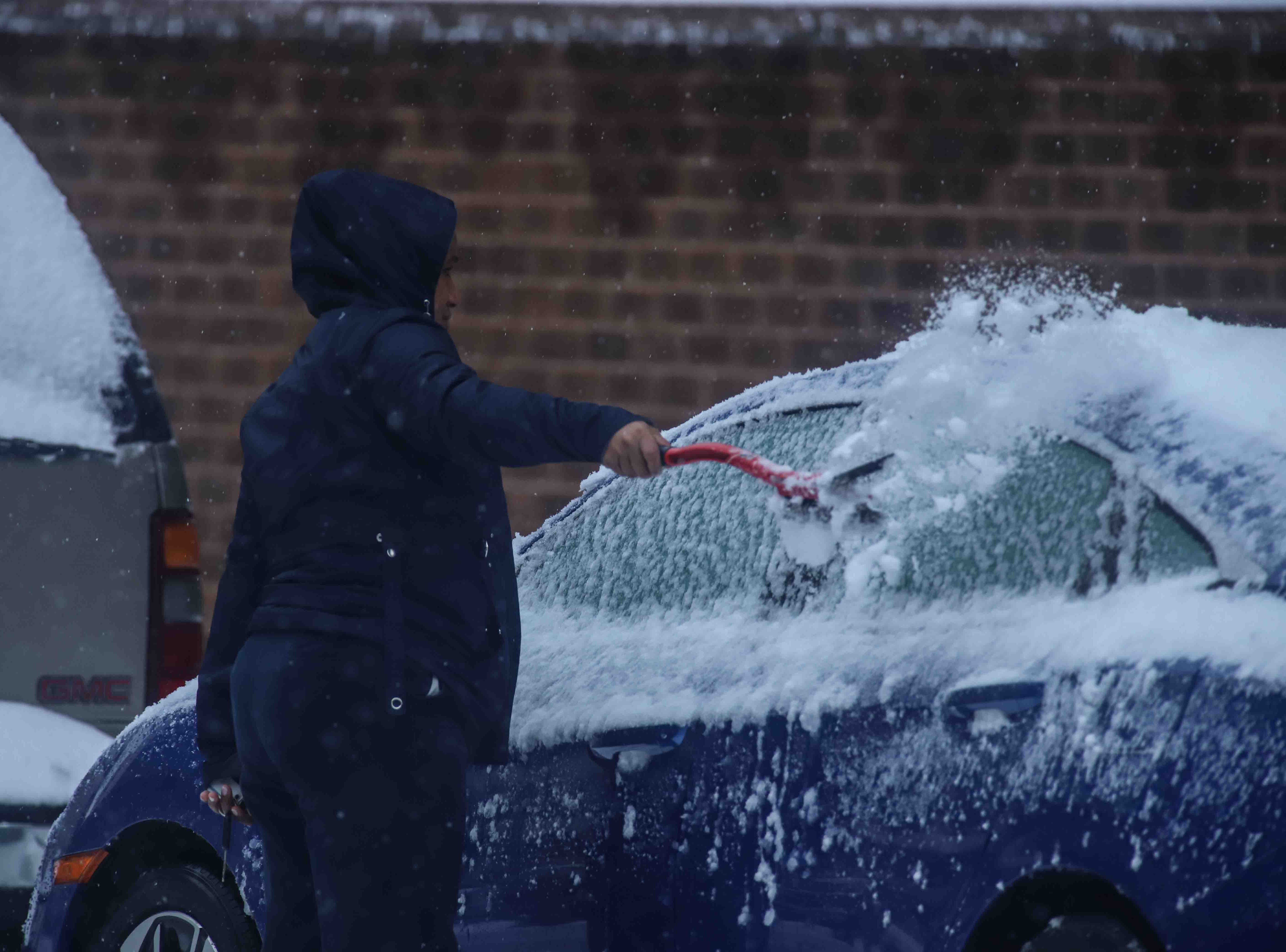 A pedestrian removes snow from her car on Thursday, Nov. 15, 2018, in Wilmington.