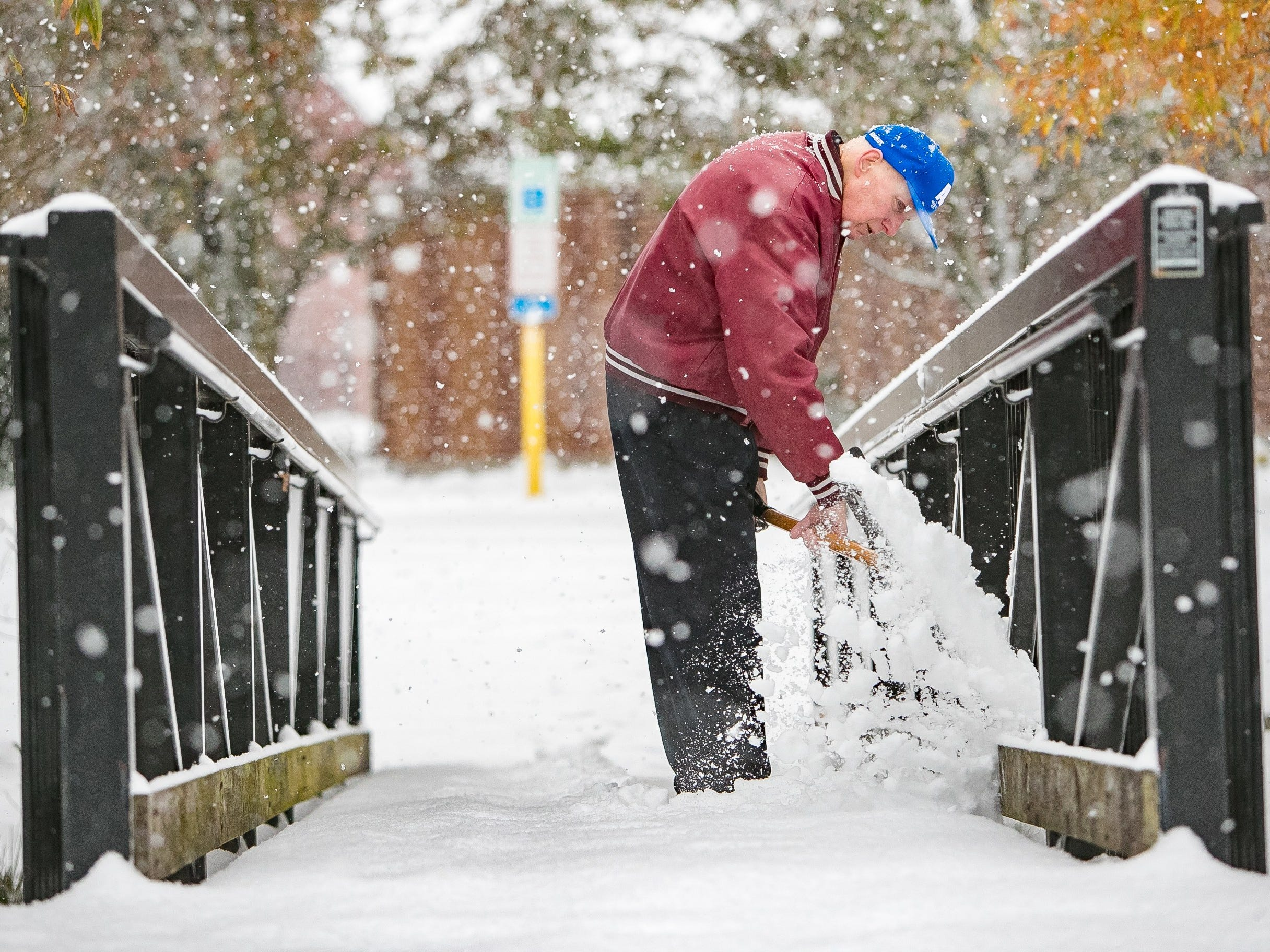 """""""I wasn't expecting this"""", says Fred Long with Hockessin Fire Hall as he shovels snow off the walk bridge in Hockessin as snow rolls into Delaware and the surrounding area."""