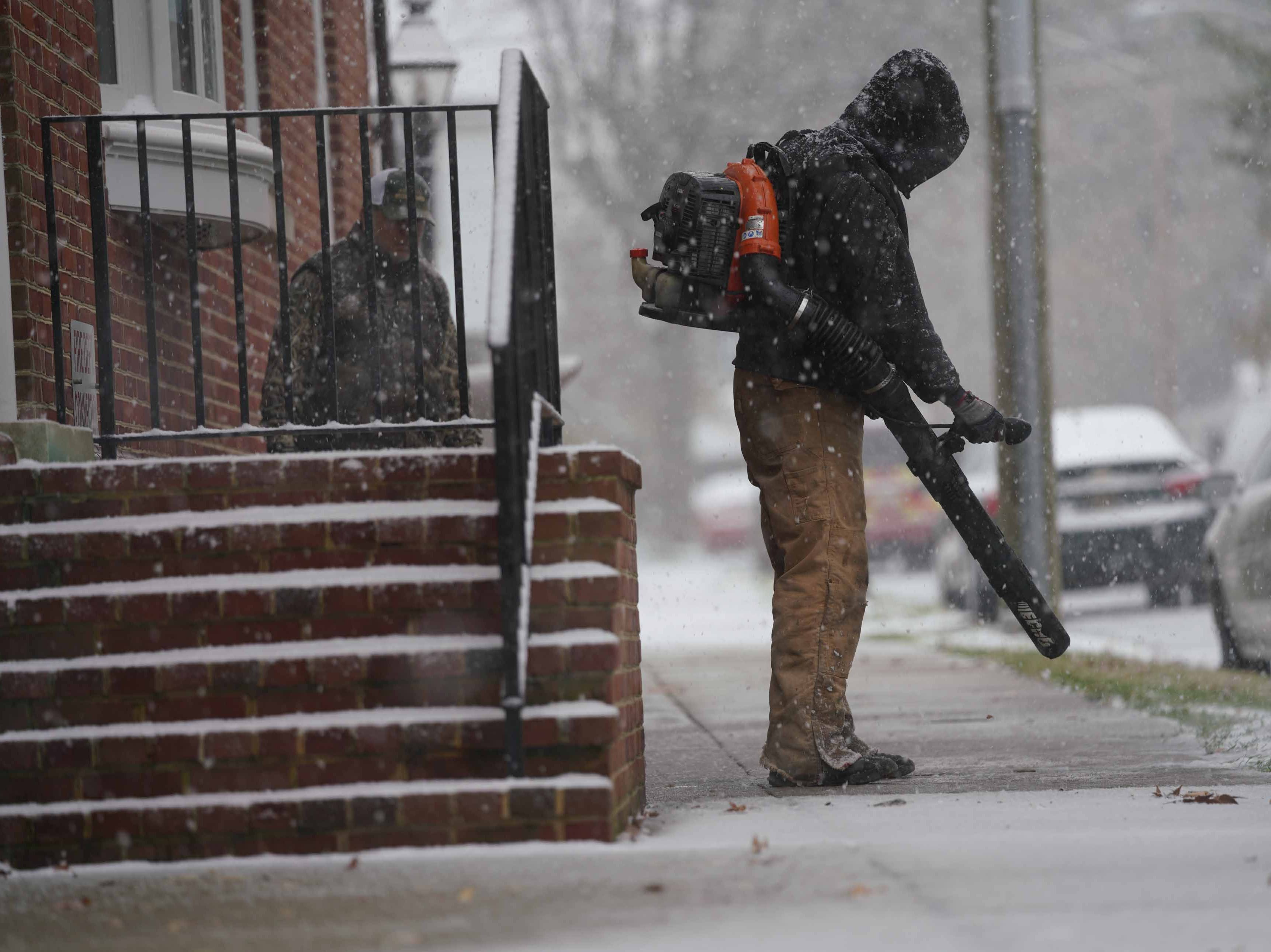 Workers help clear snow from sidewalks on E. 5th St. in Old New Castle on Thursday morning.
