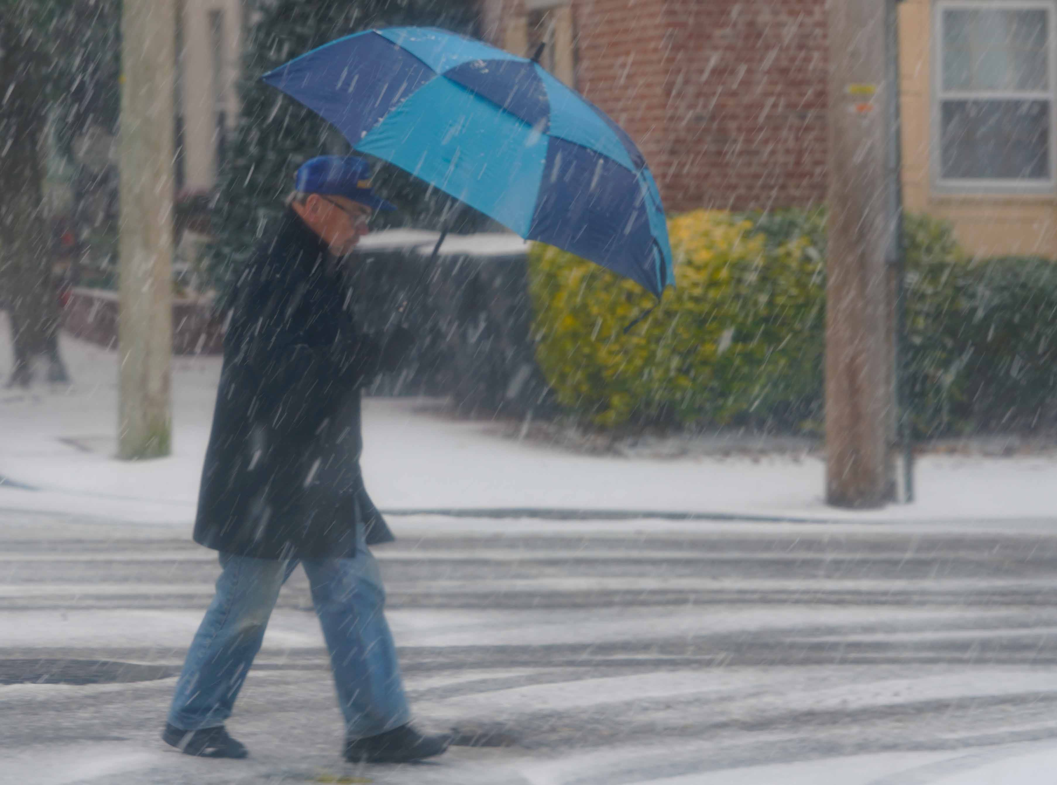 A man takes cover under an umbrella in Old New Castle on Thursday morning as snow falls along Delaware Street.