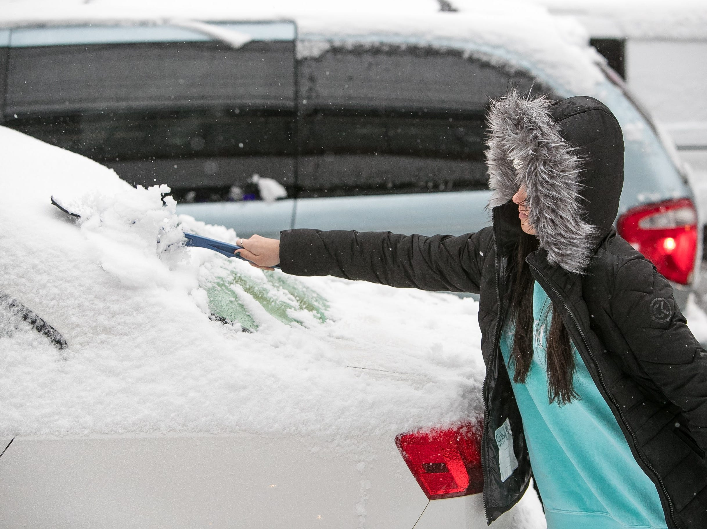 A woman clears snow from her car in Newark as snow rolls into Delaware and the surrounding area.