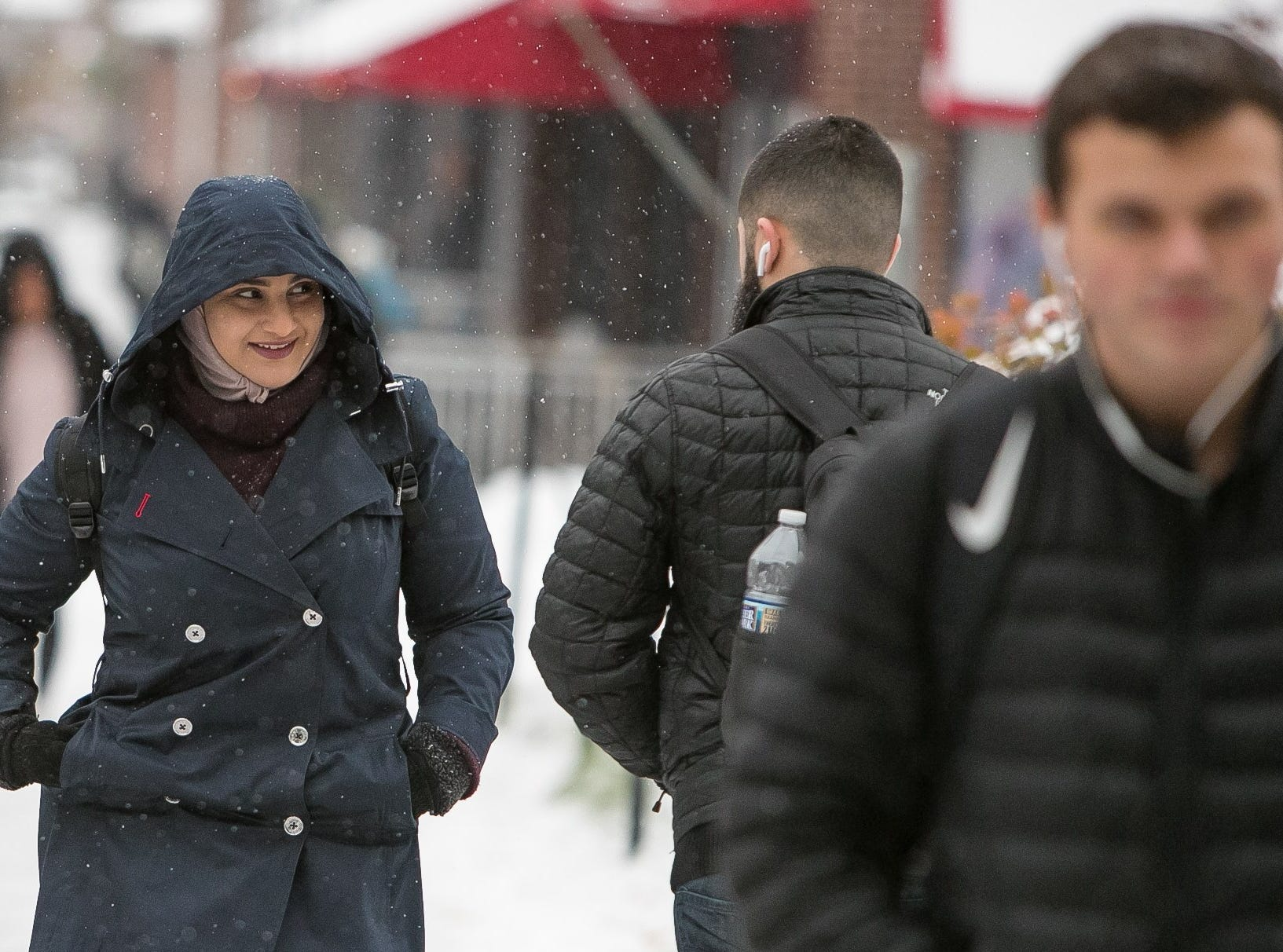 A woman walks along Main Street in Newark where classes at the University of Delaware closed at 2:30pm.