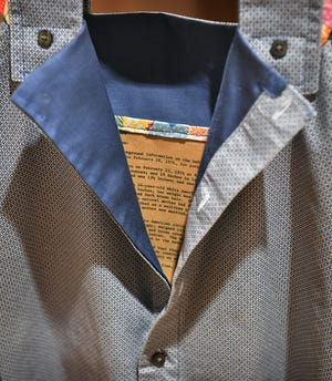 Adoption paperwork is sewn into a girl's dress as an art piece by Midwestern State University alumnus Julia Franklin, BFA 1997, in the Alumni Exhibition marking the 40th anniversary of the Fain Fine Arts Center at MSU Texas.