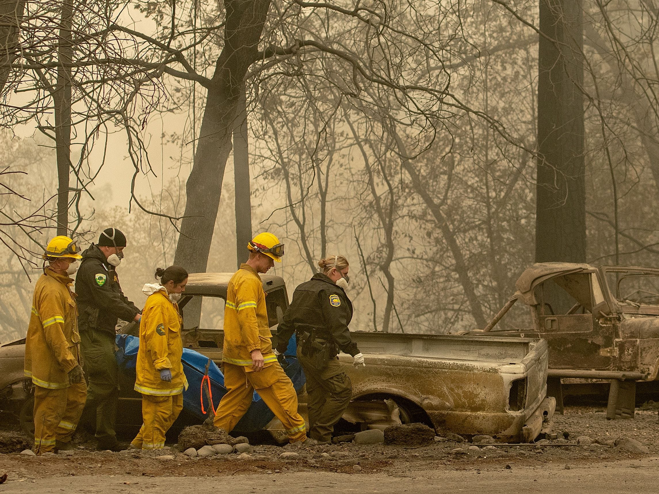 Rescue workers carry a body away from a burned property in the Holly Hills area of Paradise, Calif. on Nov. 14, 2018.
