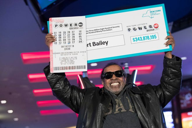 Robert Bailey displays large replicas of his winning ticket and the check he earned.