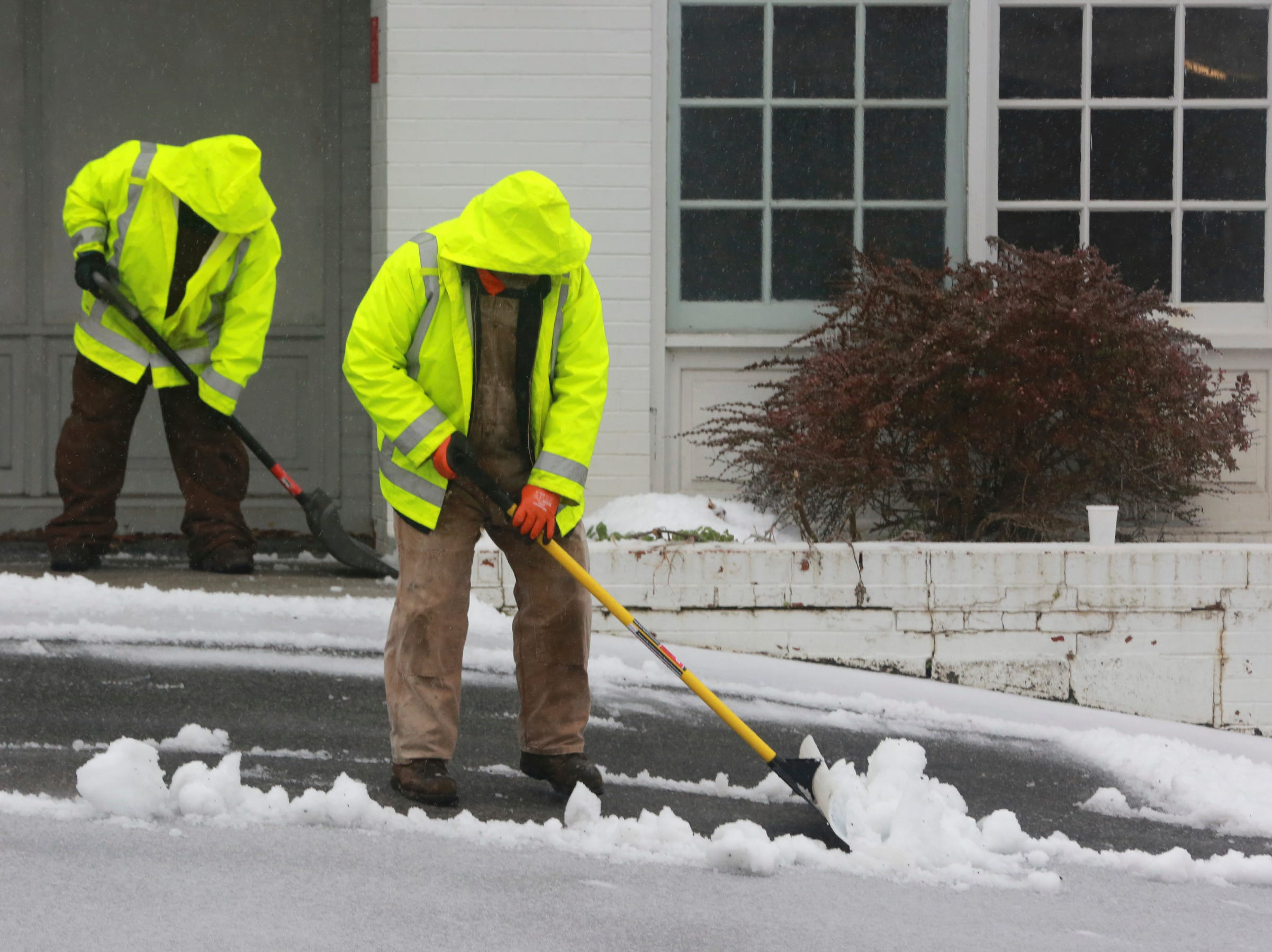 Lewis Dameron, left and Paul James, of Montgomery County General Services, shovel the steps and parking lot of a county property on North Franklin Street in downtown, Christiansburg, Va., Thursday, Nov. 15 2018. A pre-winter storm moved across the eastern half of the country Thursday, slamming parts of the South and lower Midwest on the way.