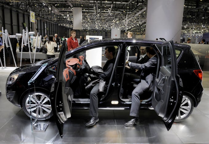 People sit inside the new Meriva by German carmaker Opel as it is displayed on March 3, 2010, during the third press day at the 80th Geneva International Motor Show at Palexpo in Geneva.